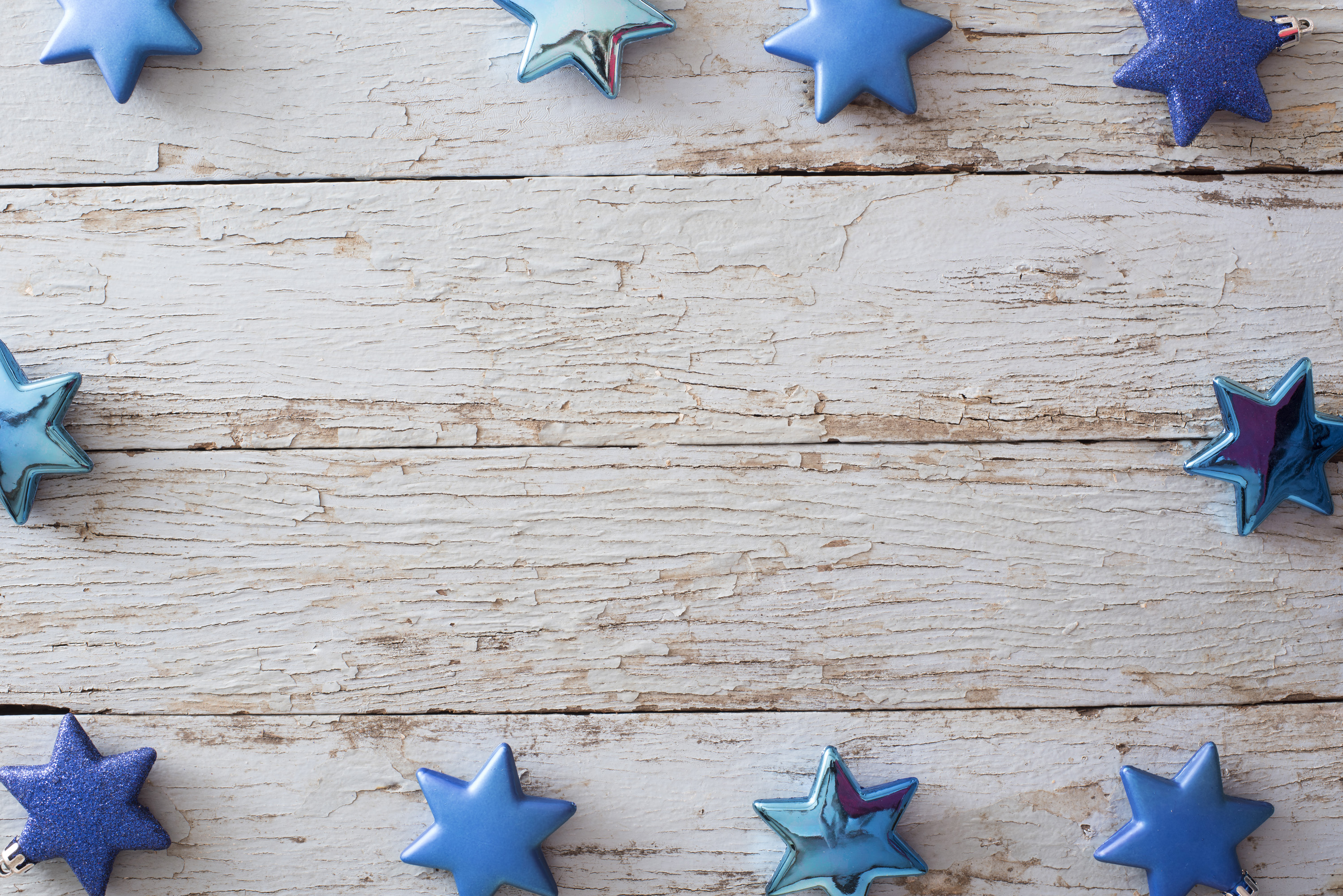 Decorative blue star Christmas border or frame on old rustic weathered textured wood around a central copy space for your holiday greeting