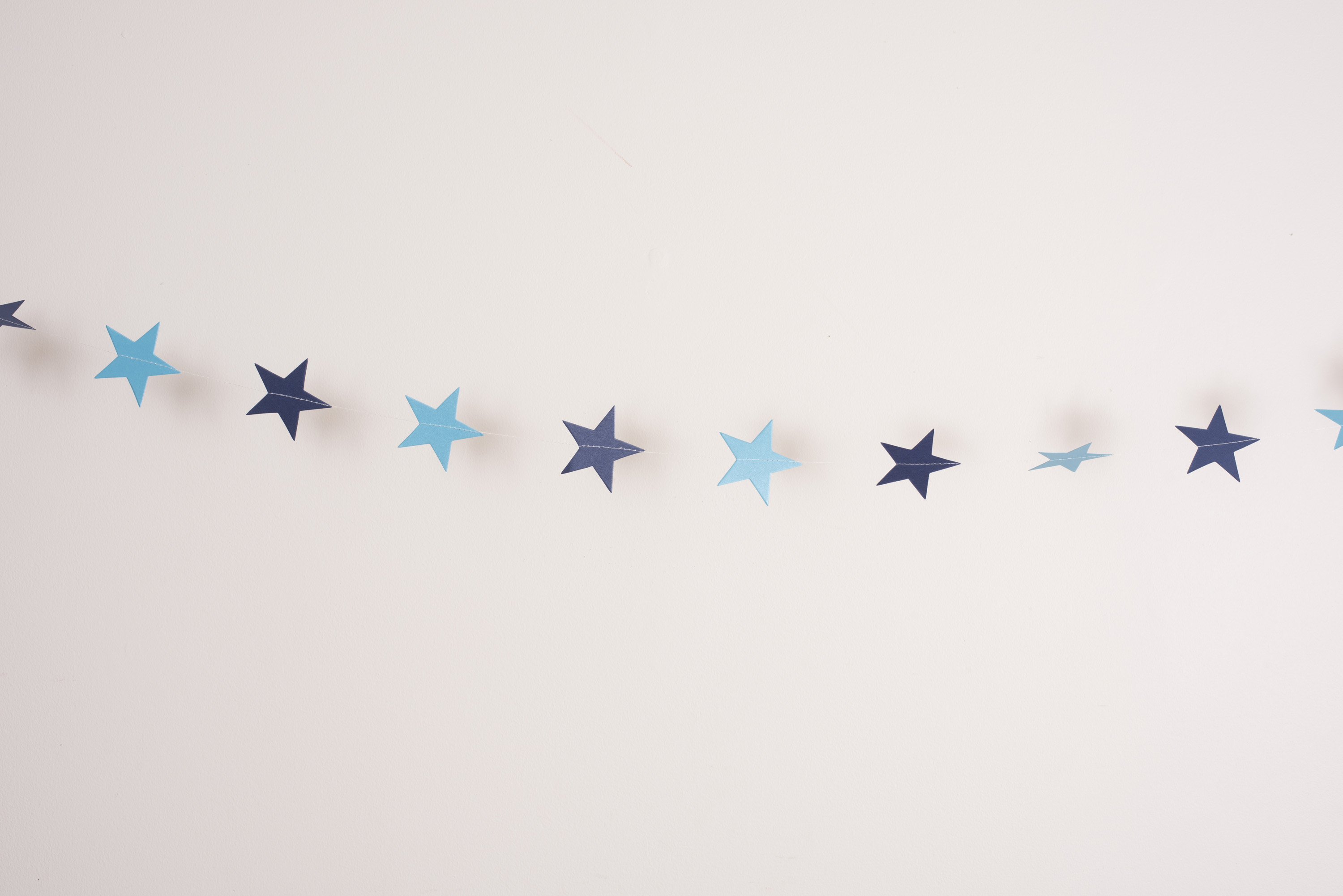 Delicate chain of small blue Christmas stars strung across a white background with copy space for your seasonal greeting