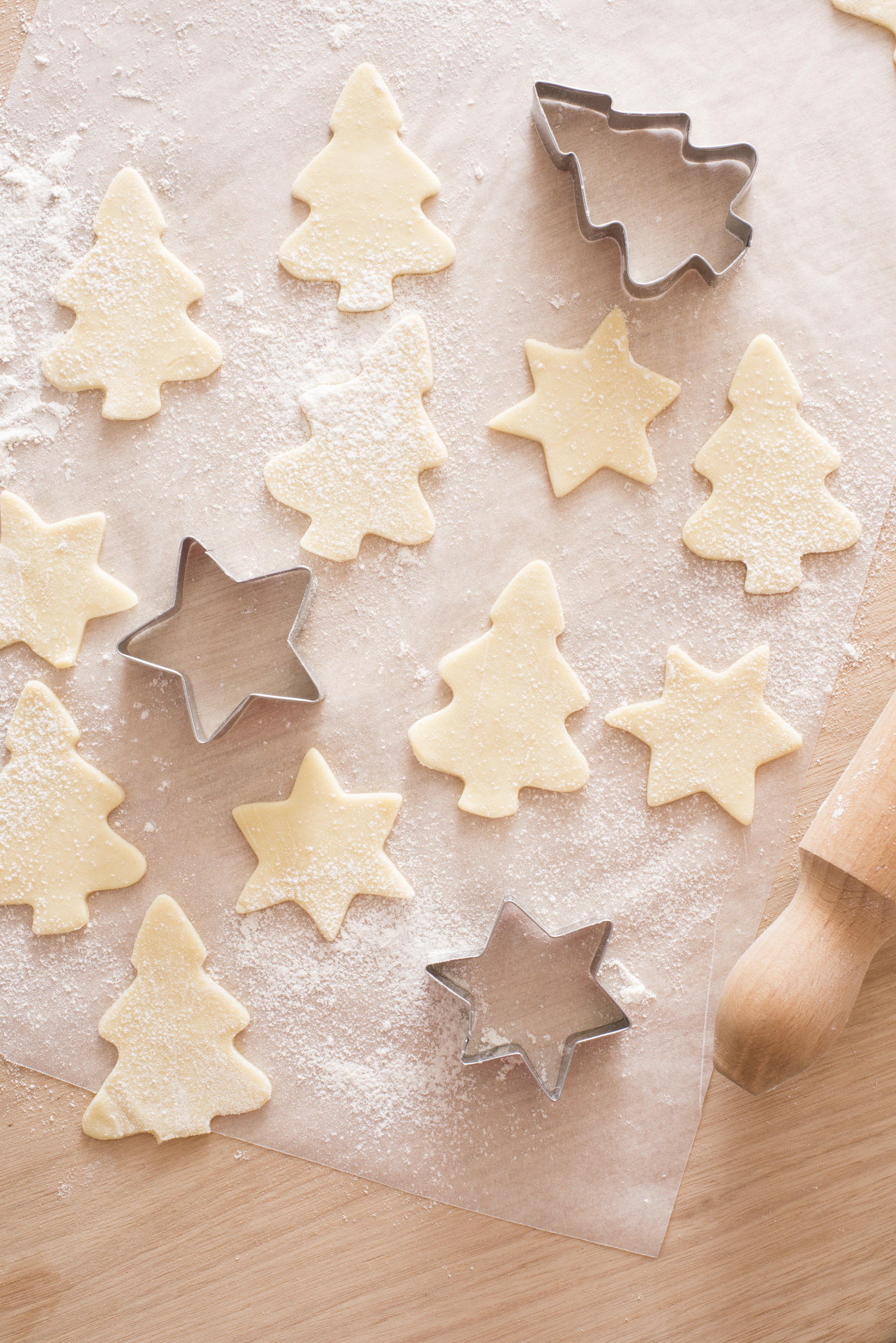 Christmas baking of traditional festive cookies in tree and star shapes with an overhead view of metal cookie cutters and cut out raw pastry on floured paper on a kitchen counter