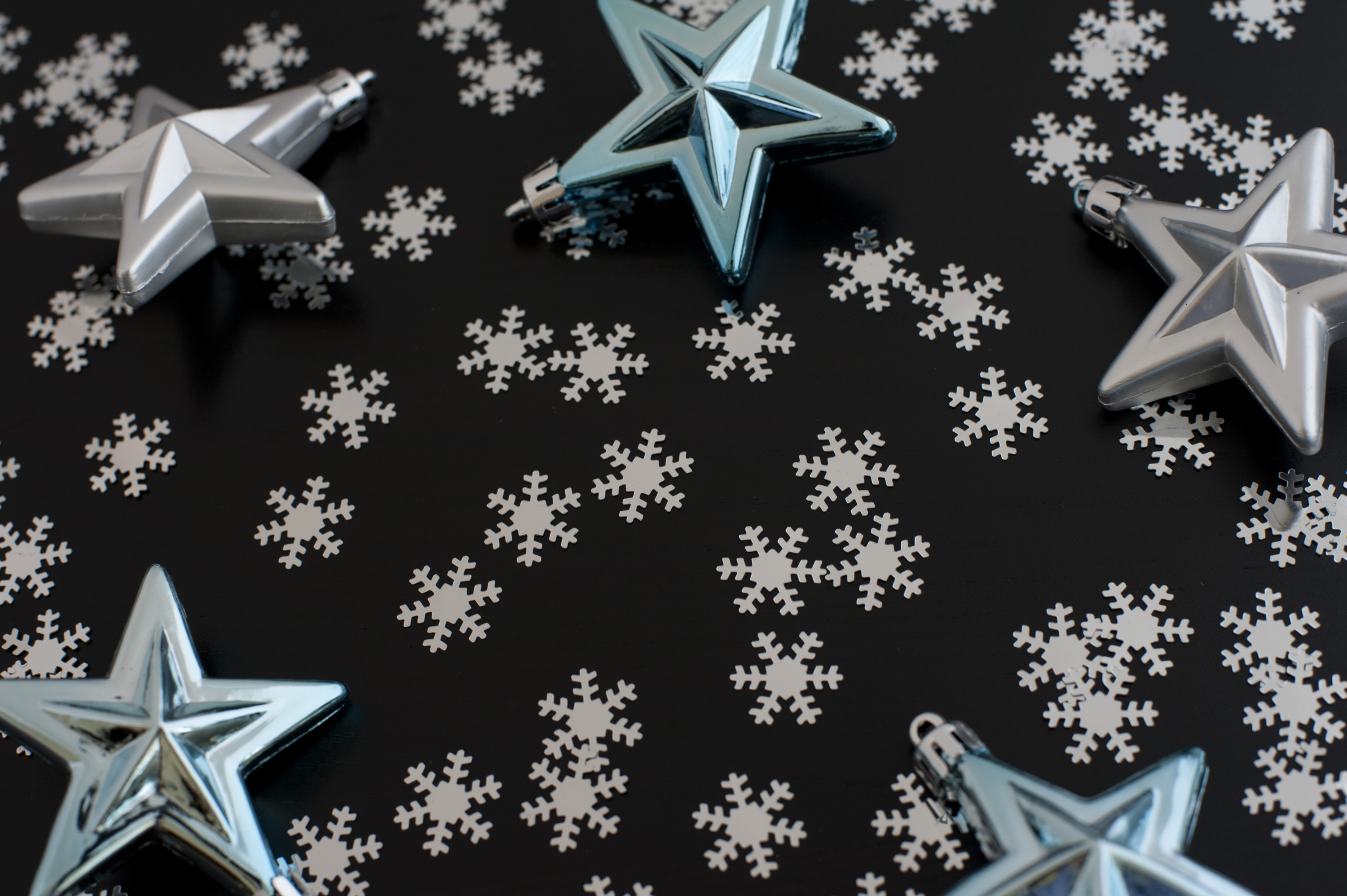 Christmas star background with scattered winter snowflakes forming copyspace for your greeting or message