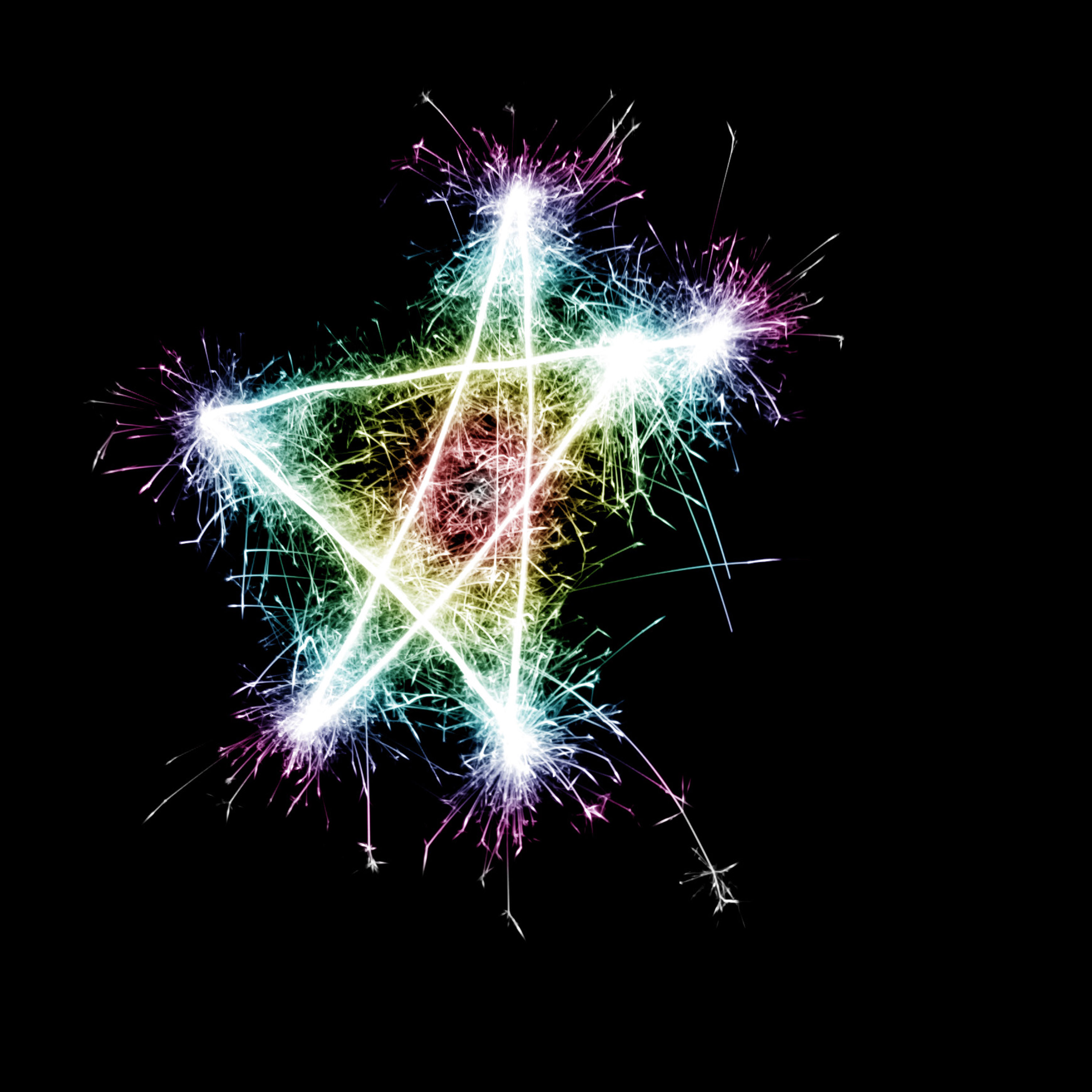 a bright multicolored sparking star symbol on a black background