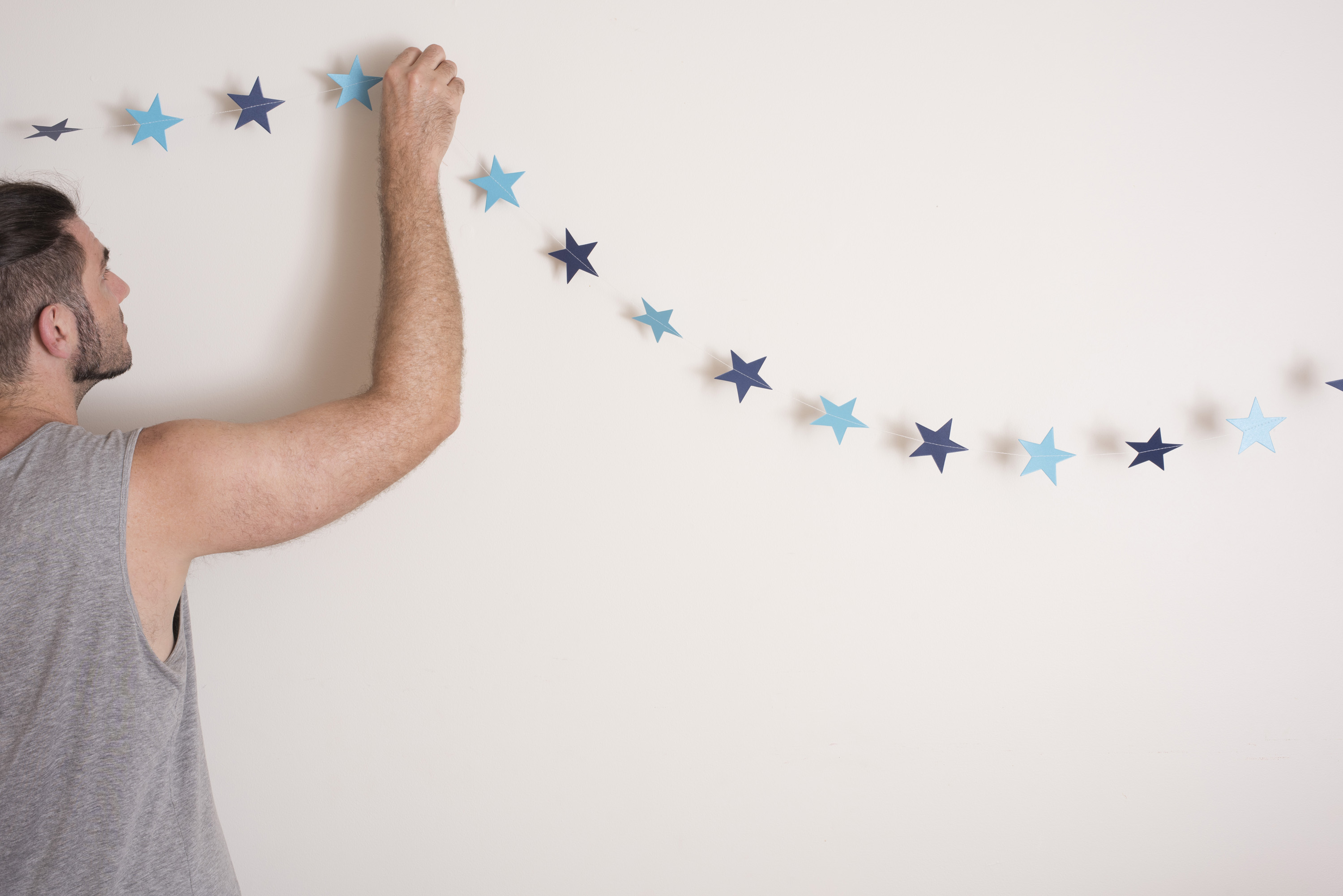 Man hanging Christmas decorations at home attaching a garland of festive blue stars to a white wall with copy space