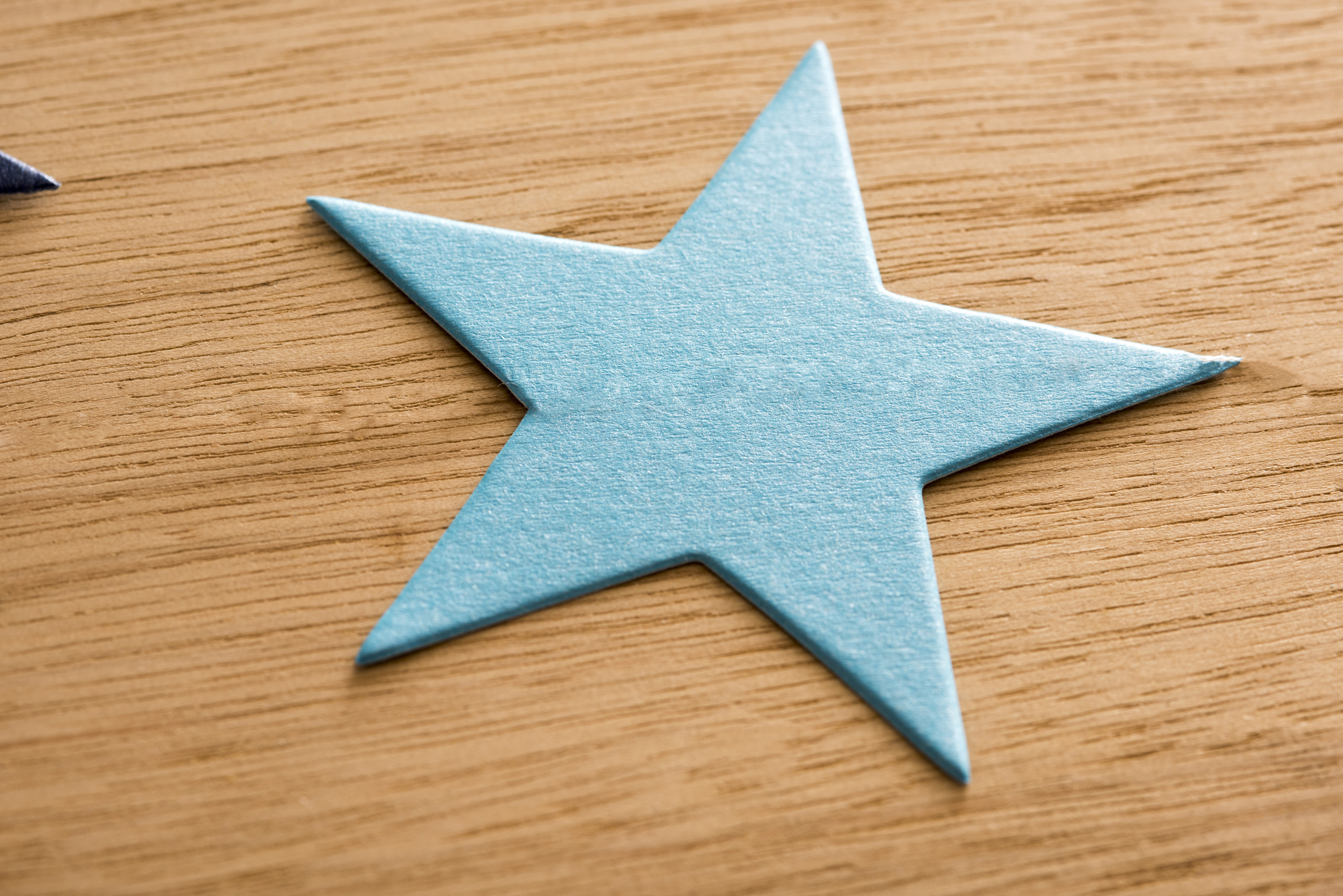 Blue green Christmas paper star on a textured wooden background with woodgrain