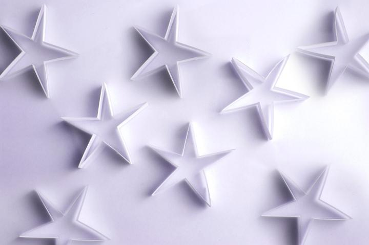 Scattered paper stars on a white background form a lovely delicate ...