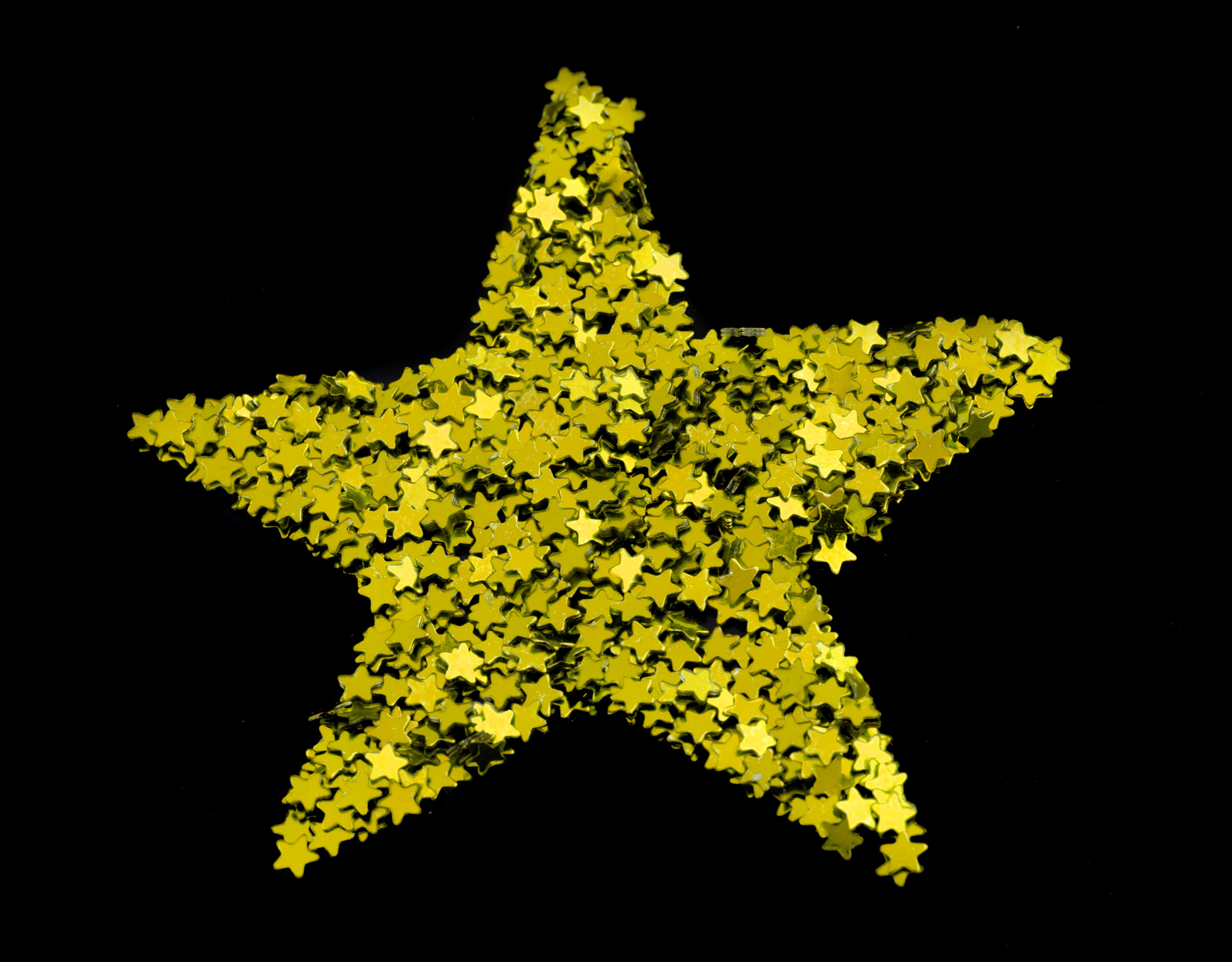 Multiple small shiny gold stars arranged to form a single large golden Christmas star on a black background
