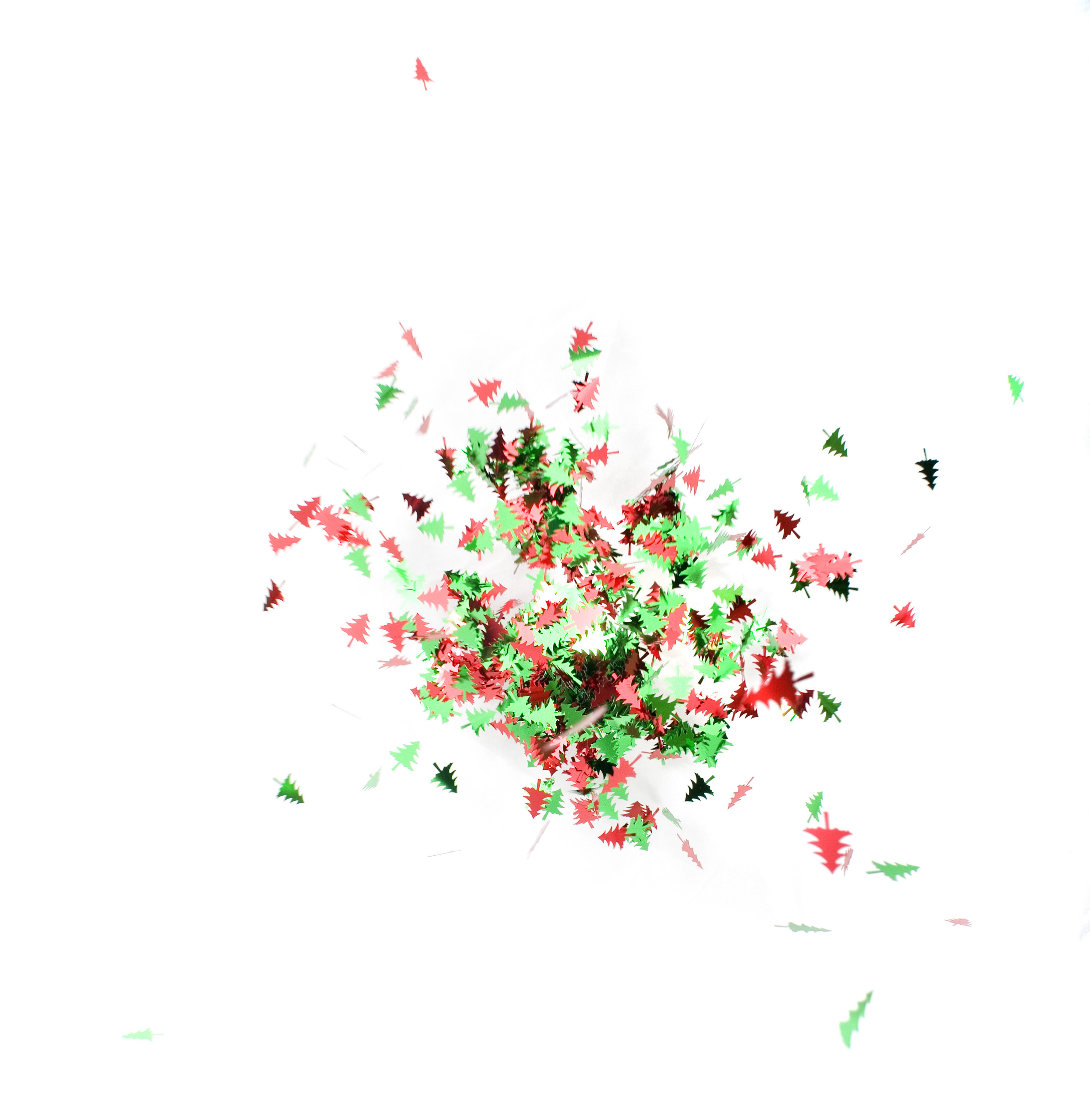 an unusual seasonal background composed of flying christmas tree shaped confetti pieces