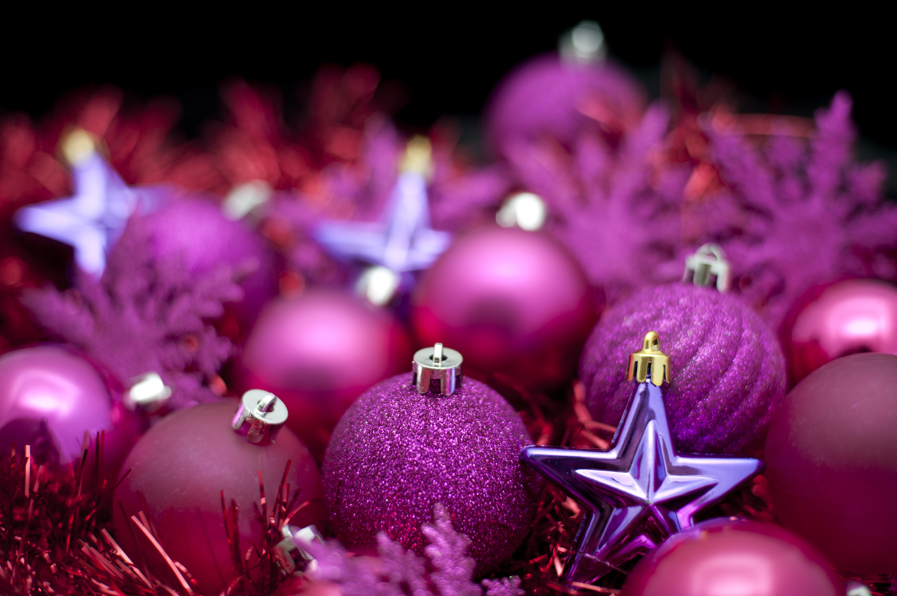 Festive background of purple Christmas decorations, baubles and stars with shallow dof