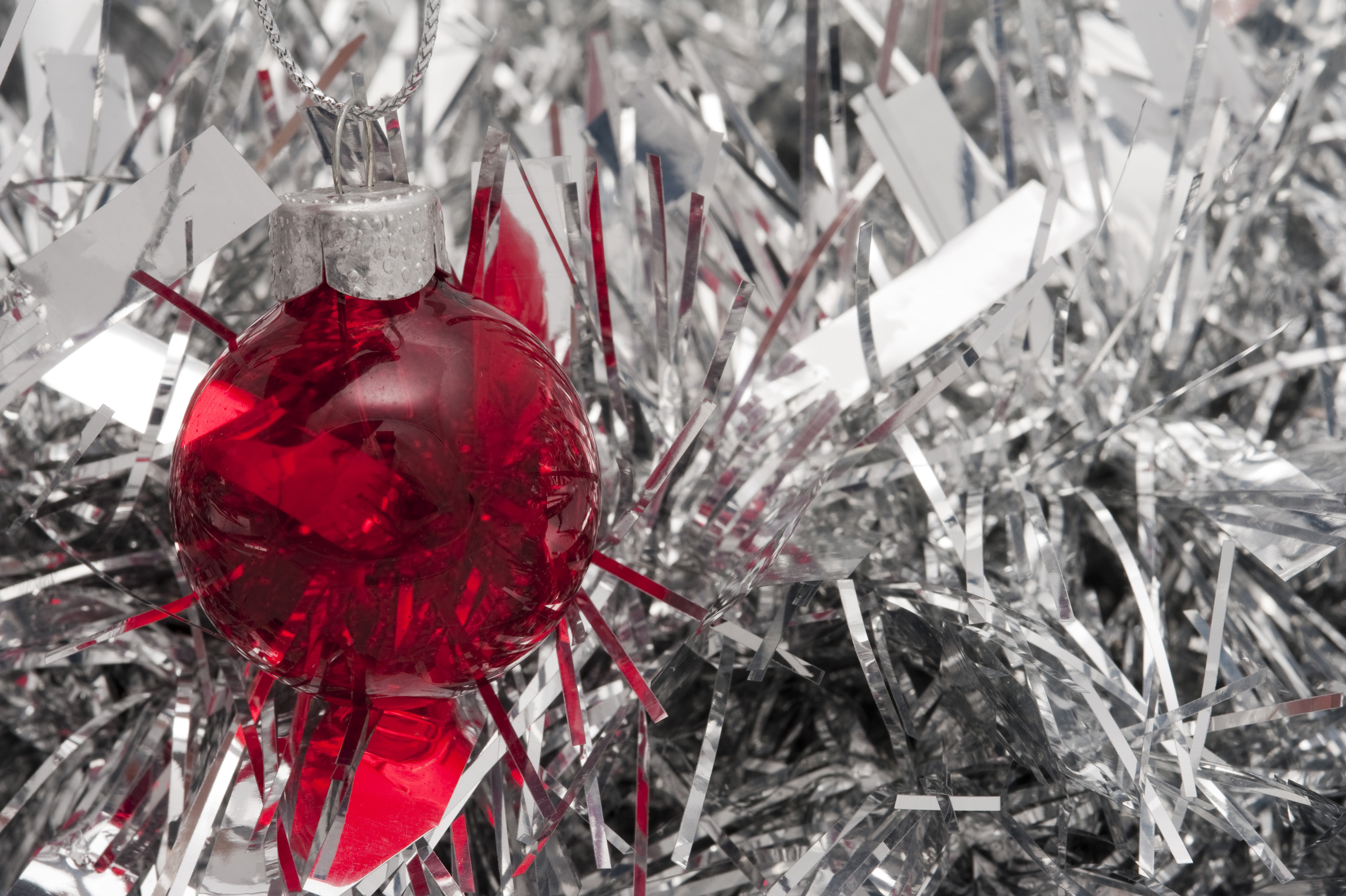 red christmas ornament on background of silver glittering tinsel
