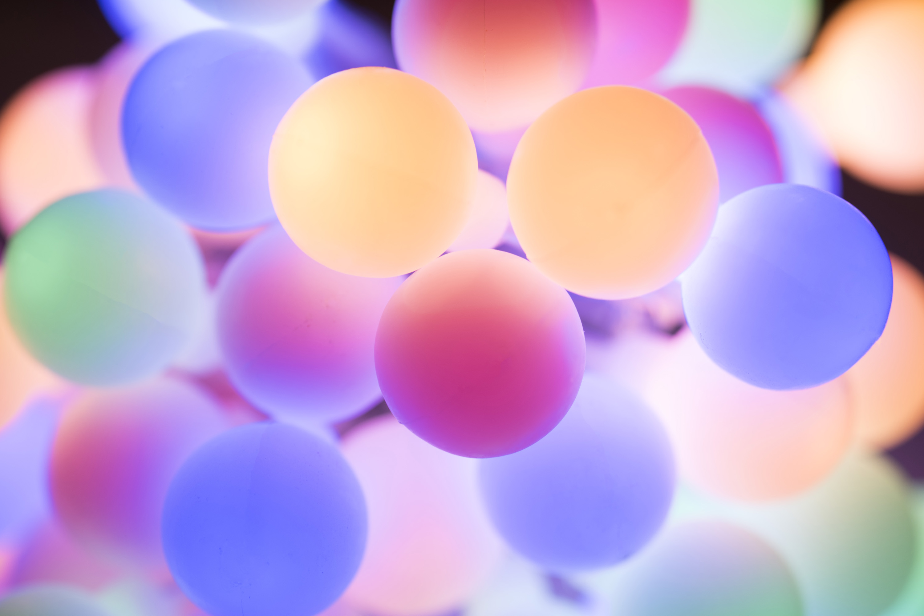 Christmas background of softly glowing colorful round lights in pastel hues in a full frame view