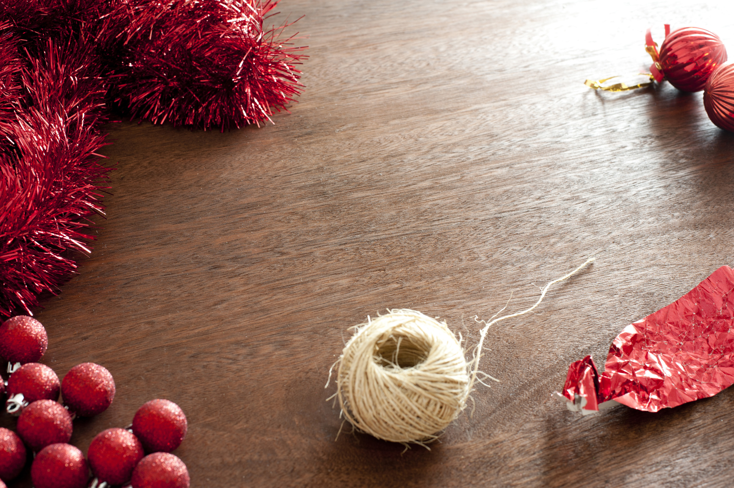 Different Christmas decorative elements on wooden table. Rope, red glare, wrap and Christmas balls