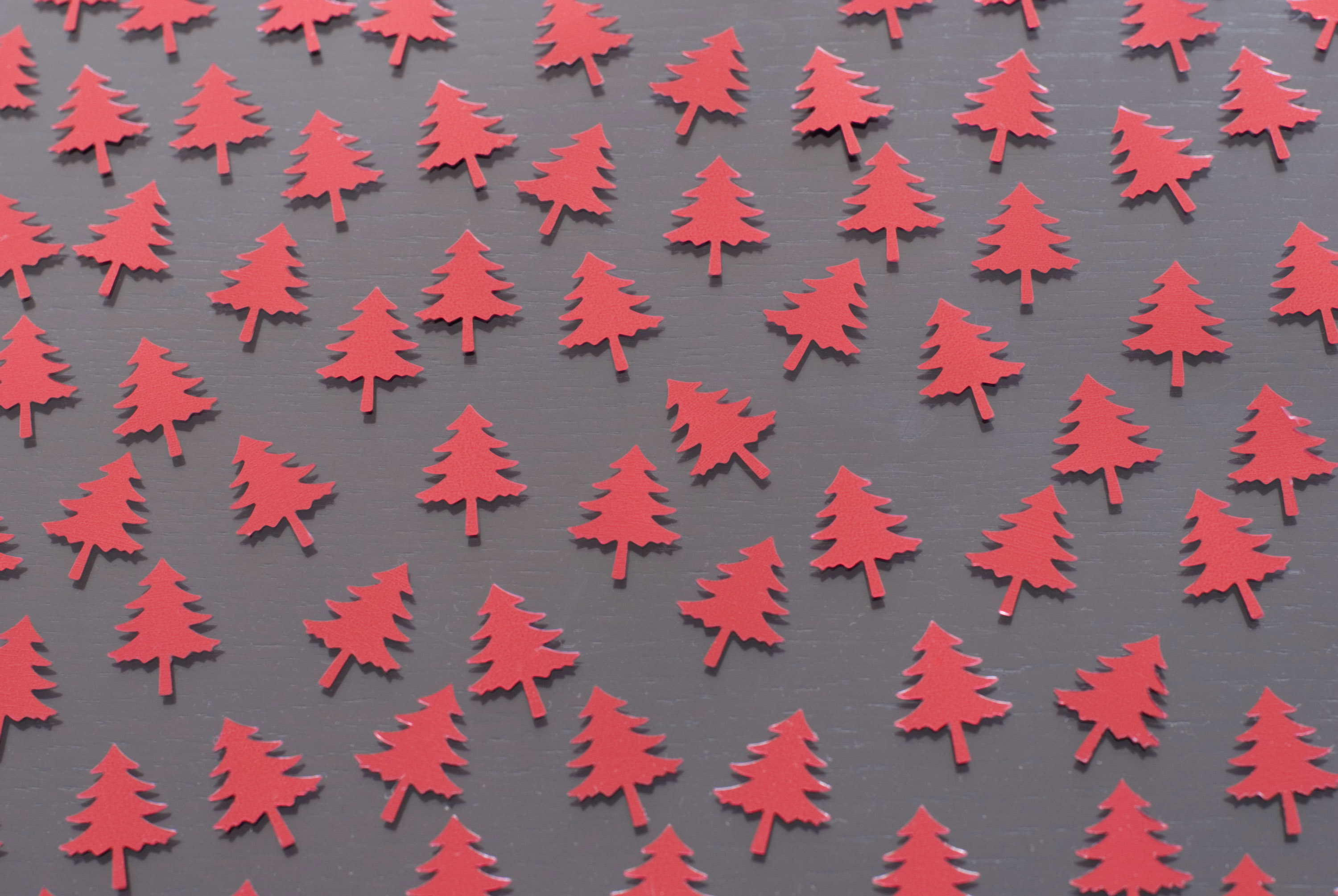 a background image of red christmas tree confetti arranged on a table top
