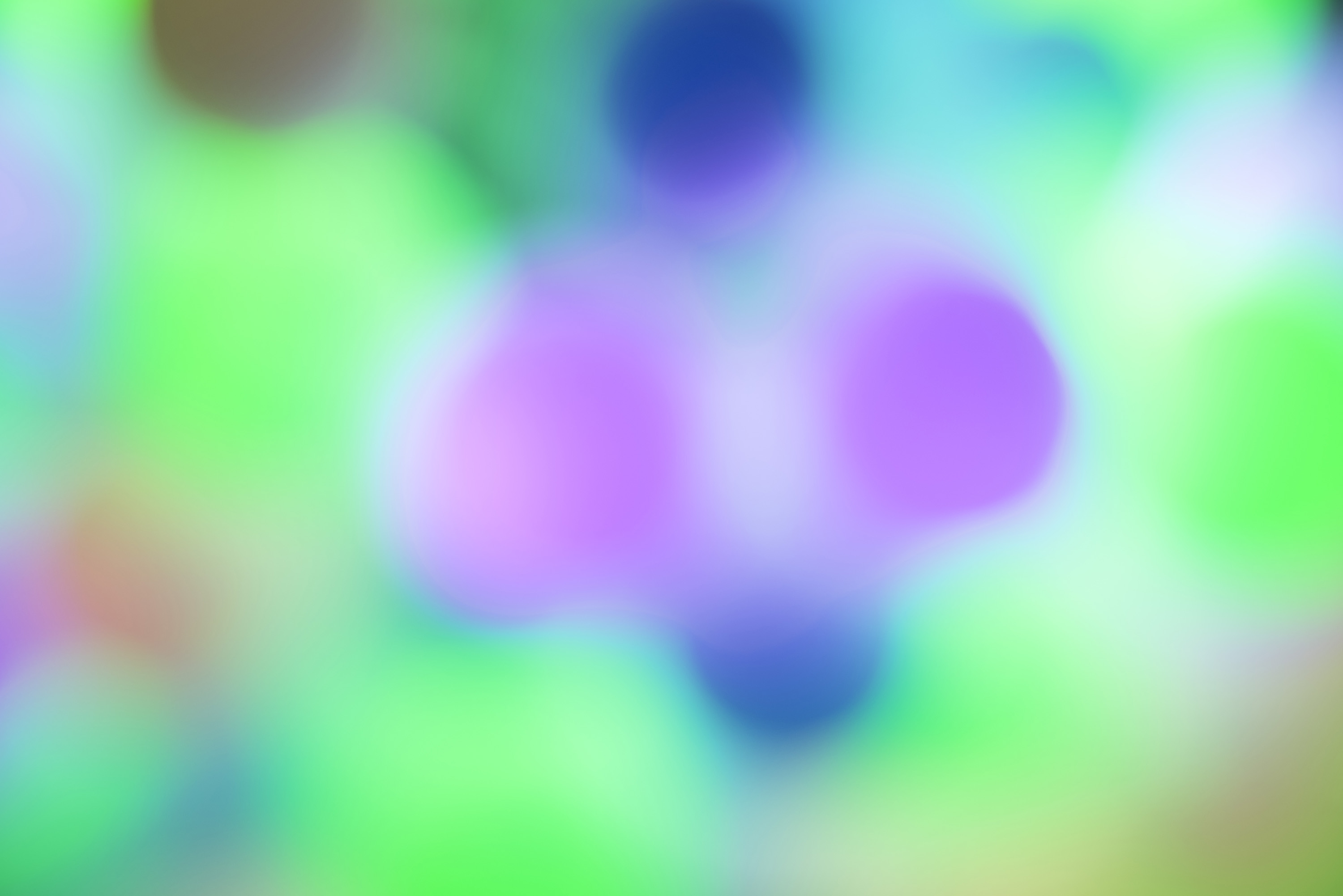 Colorful background with a soft circular bokeh in green , blue and purple of round festive lights for a party or Christmas celebration