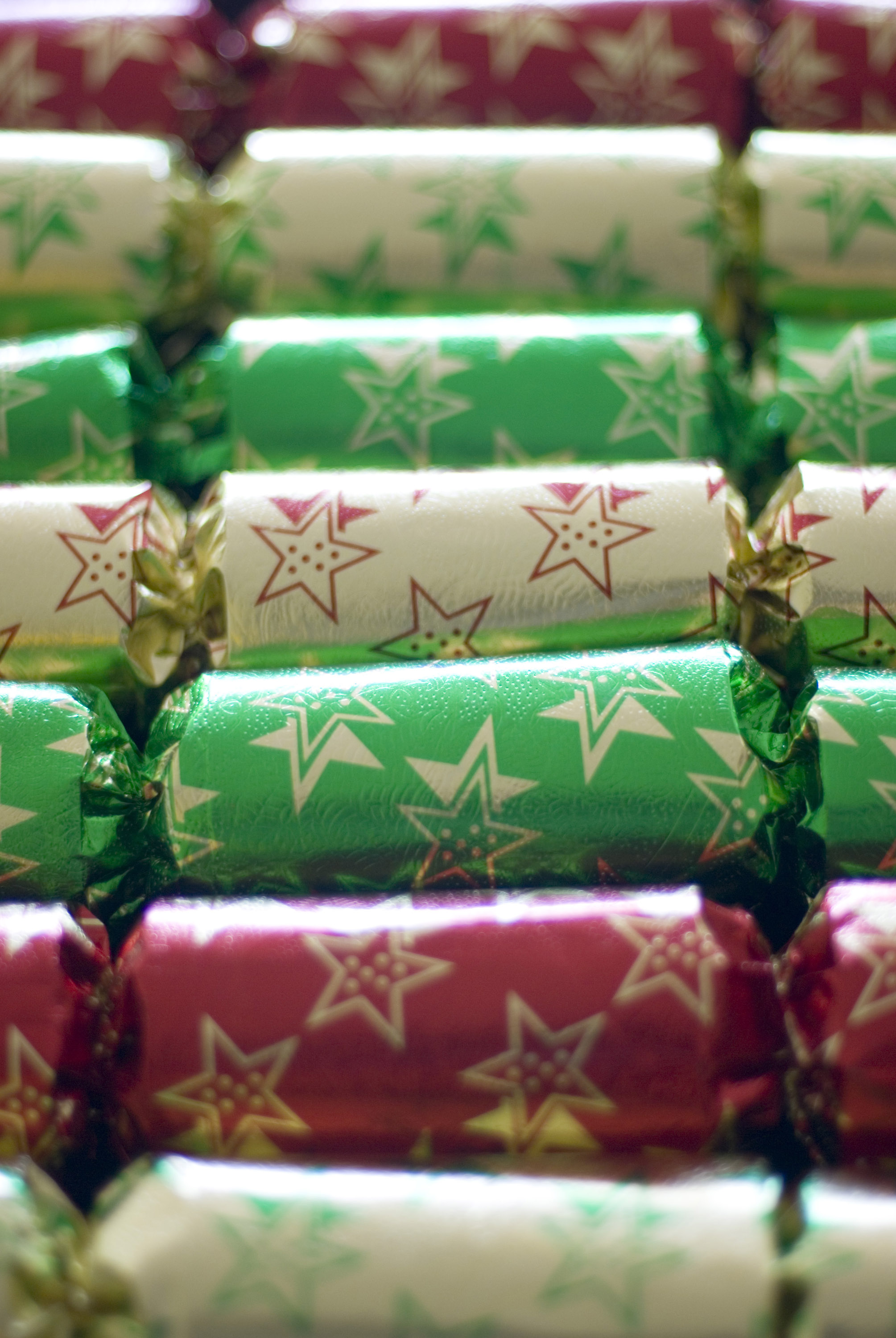 a row of christmas crackers imaged with a narrow depth of field (out of focus in the backbackground and foreground)