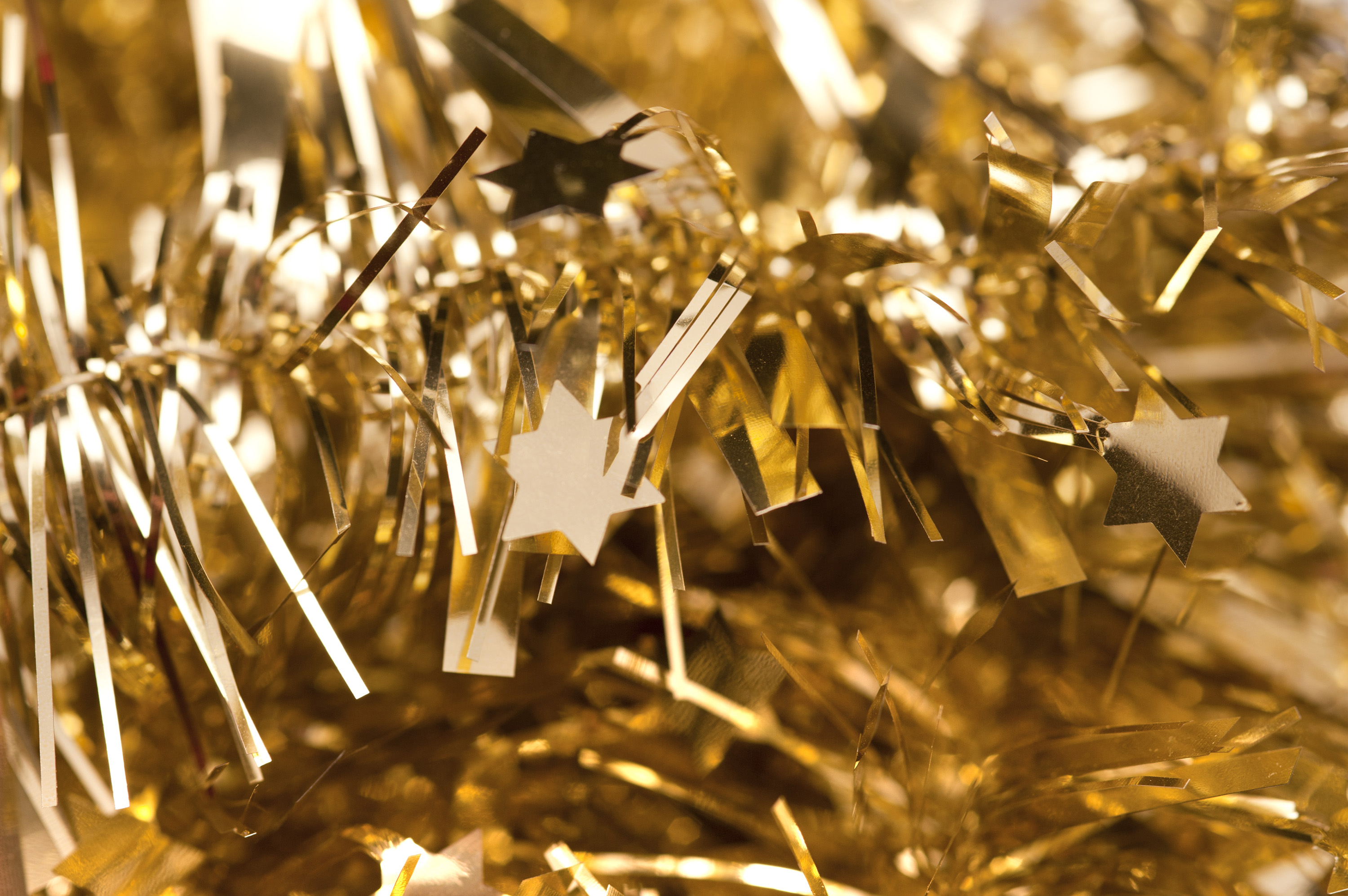 Glittering gold tinsel with little stars as a backdrop for your Christmas or festive greetings card or invitation