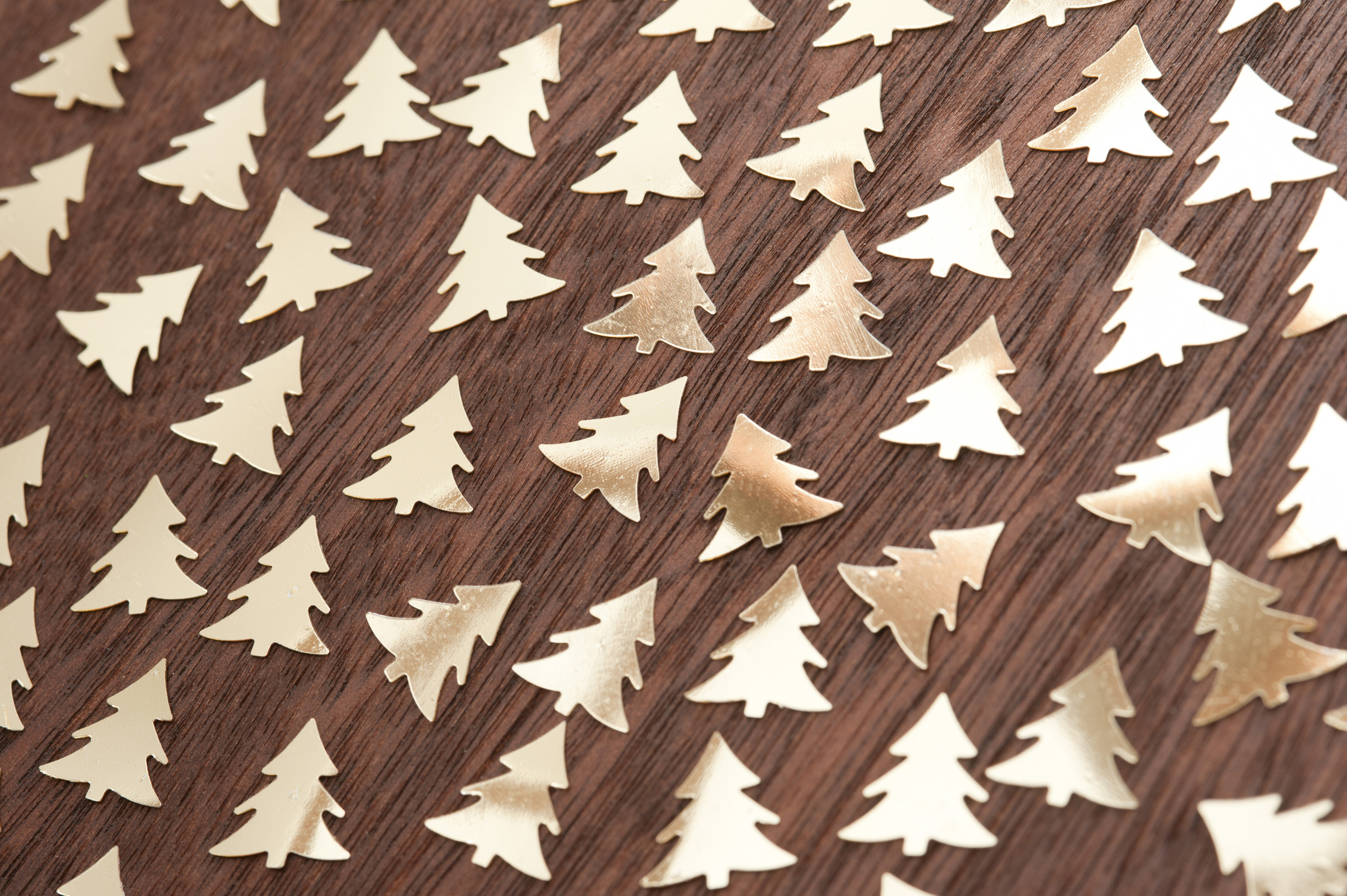 Many handmade  golden fir trees on wooden table