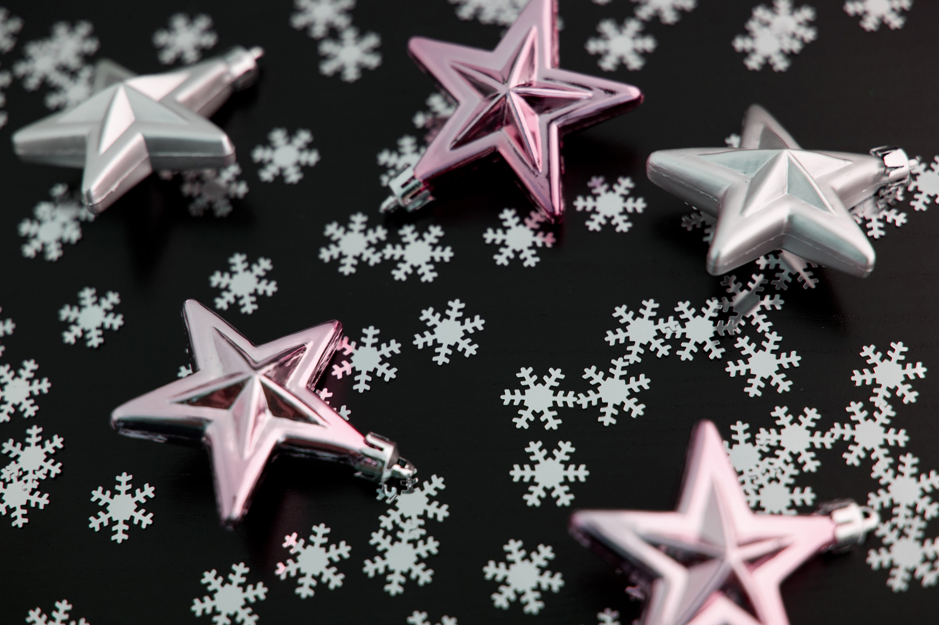 Pink stars and snowflakes randomly scattered across black for your Christmas background