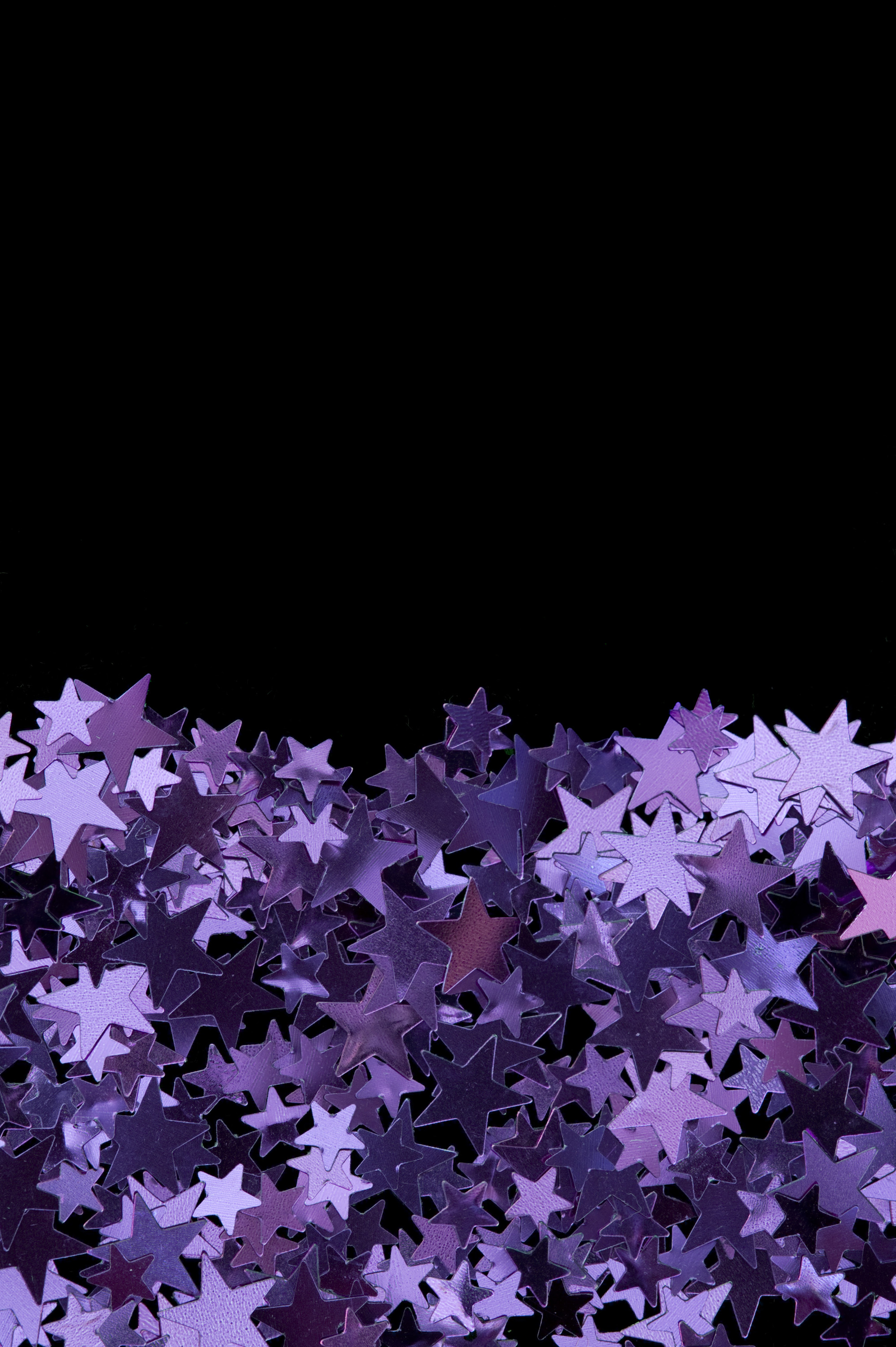 a frame half filled with colourful reflective purple star shapes of various sizes and the remainder left blank for copy