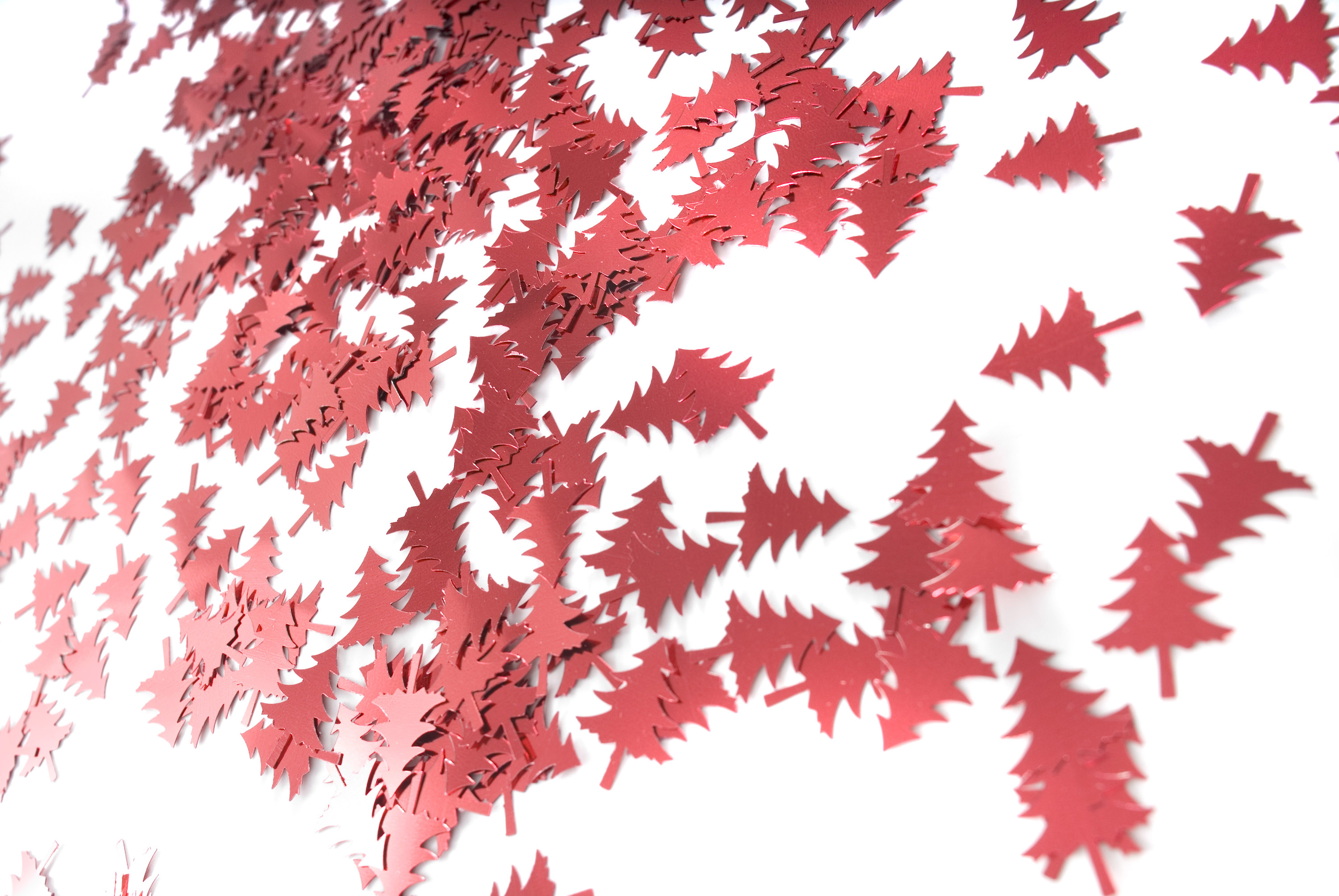 A background image of red metallic christmas tree shapes
