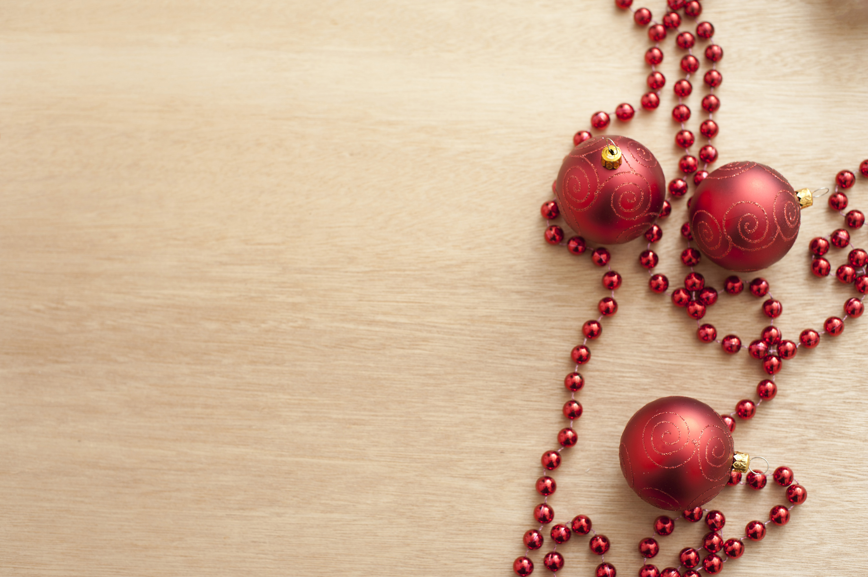 Red tree decoration and red garland lying on wooden light brown table. From above
