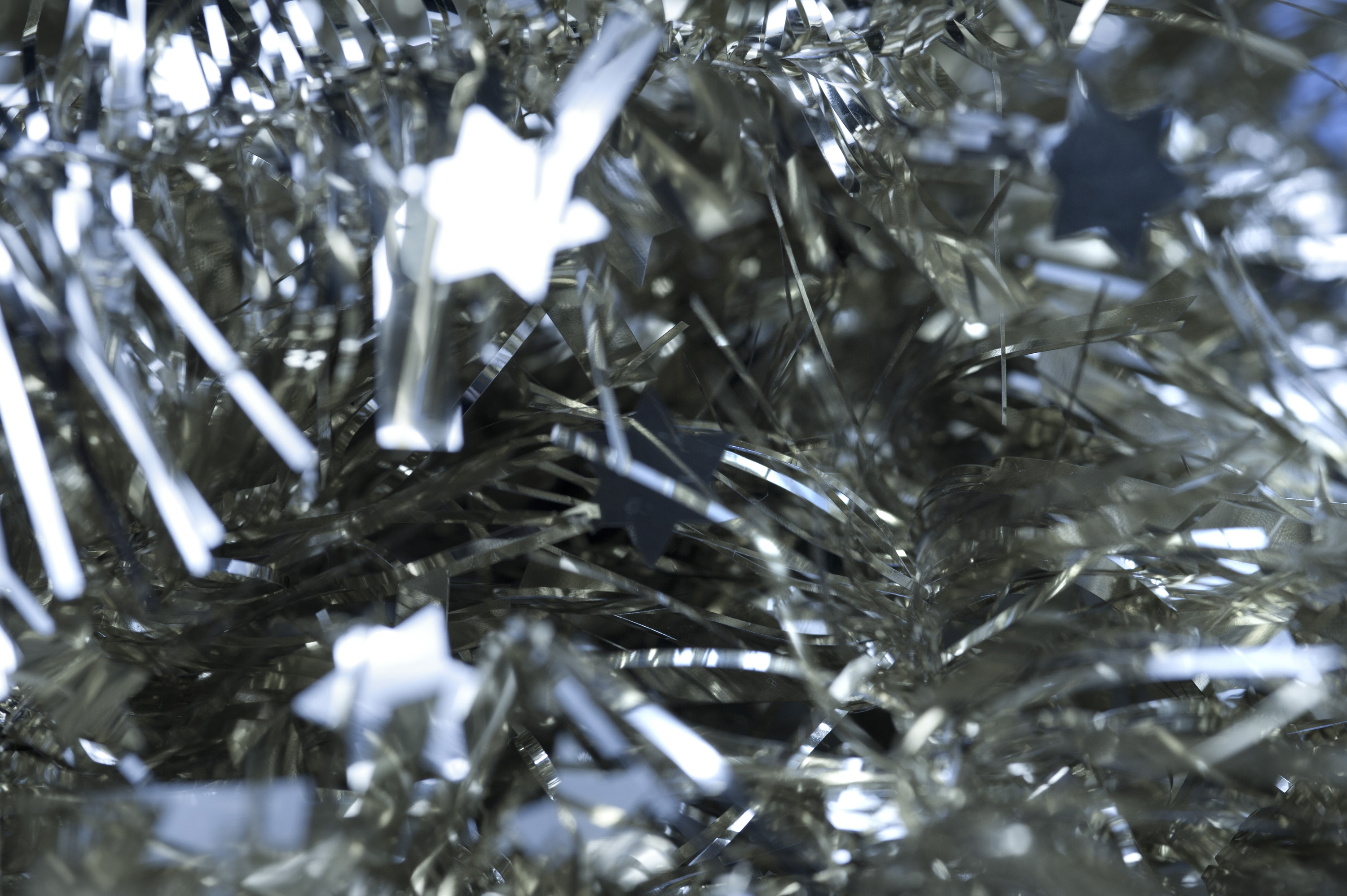 Abstract Christmas background of glittering silver tinsel with stars