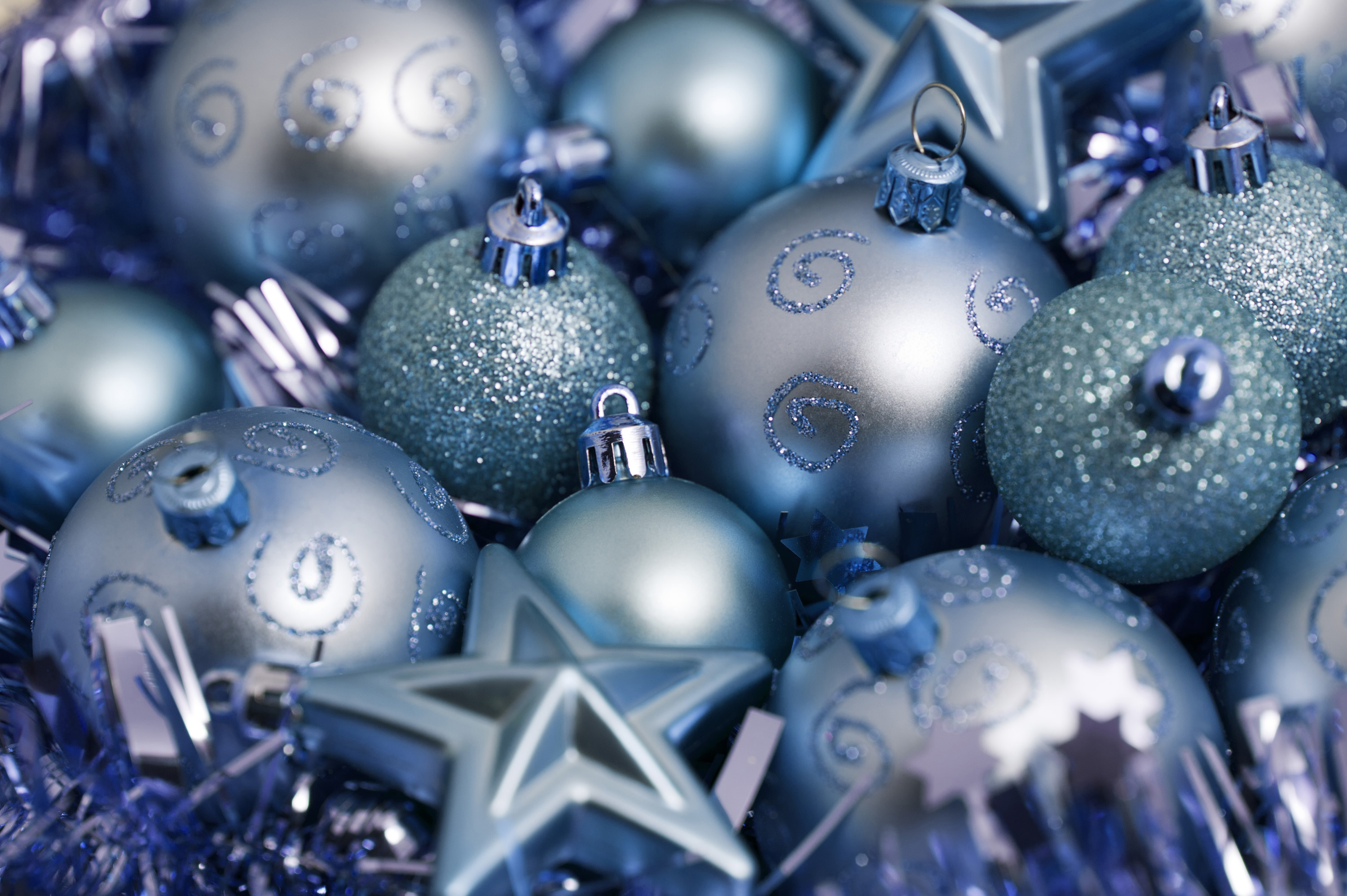 An assortment of decorative blue baubles and stars for a Christmas background or greeting