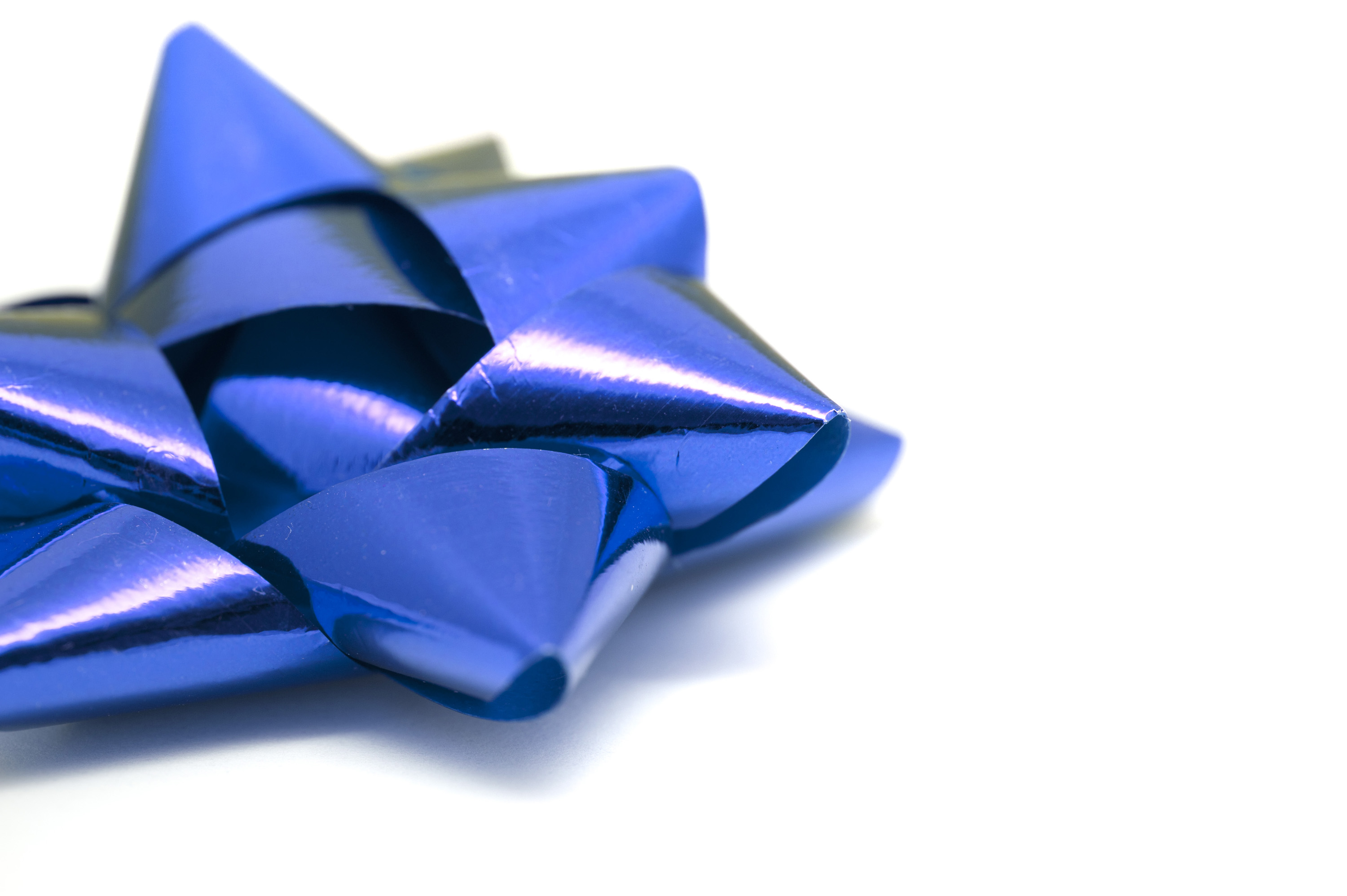 Metallic blue ribbon bow for a gift on a white background with copy space for your message or seasonal greeting
