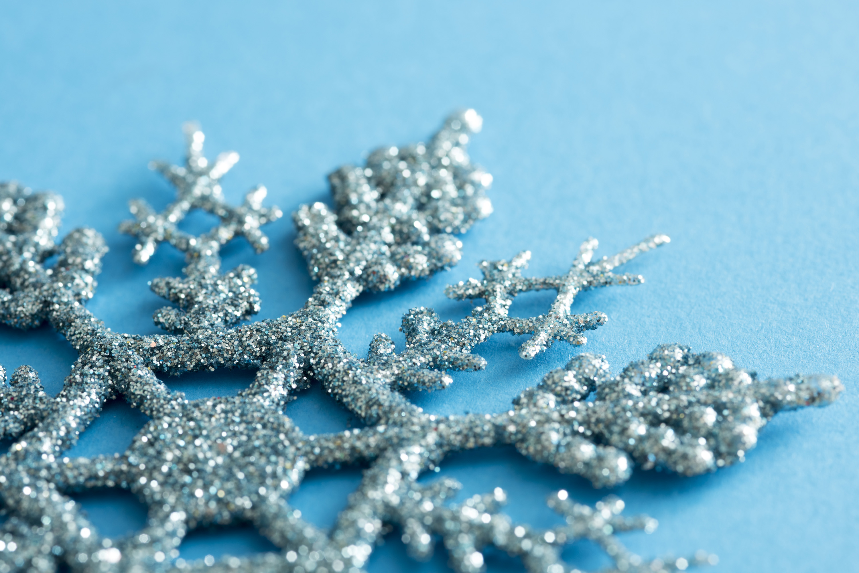 Glitter texture on a blue snowflake Christmas decoration in a close up oblique view on a matching cool blue winter background with copy space