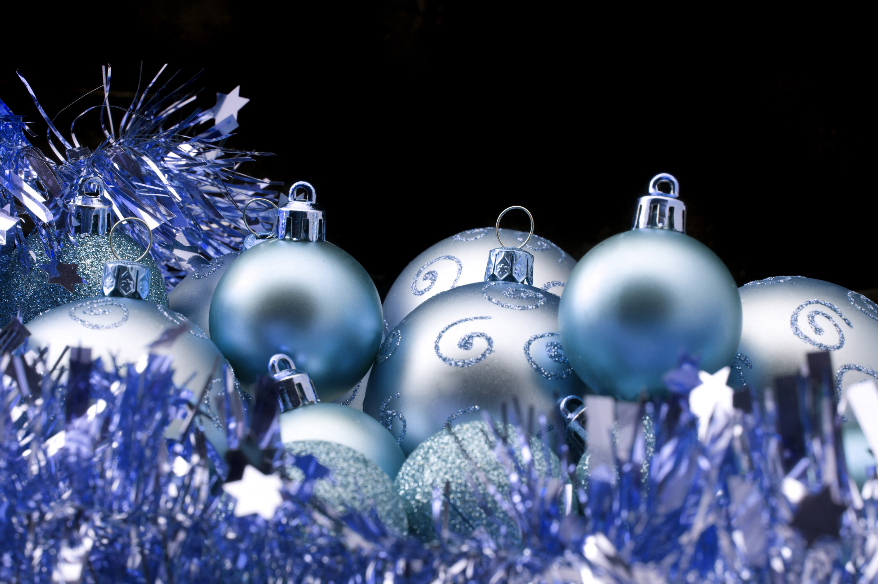 Blue Christmas tinsel and baubles on a black background with copyspace