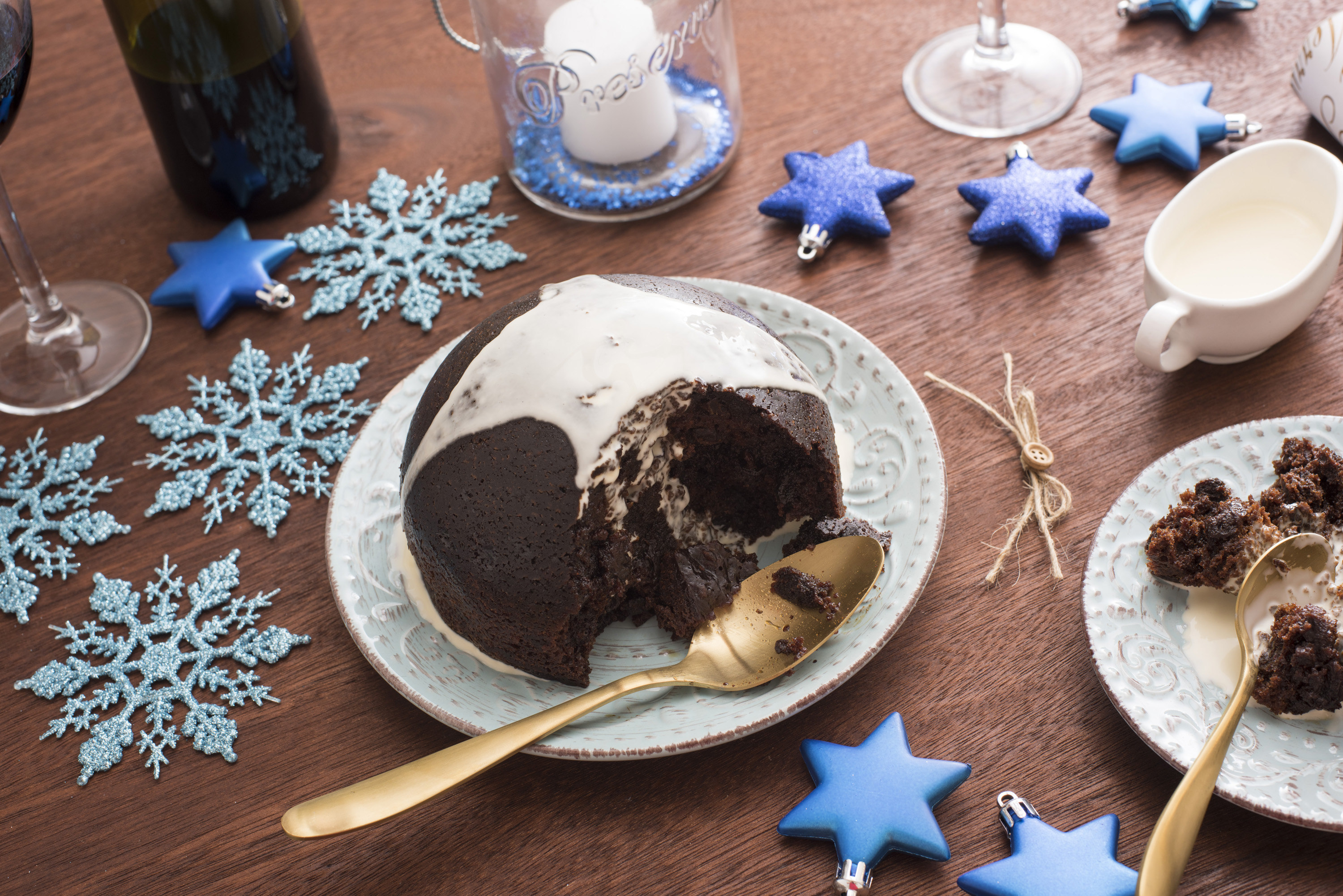 Tasty traditional fruity Christmas pudding served for dinner topped with brandy cream on a festive table with a candle, decorations and wine