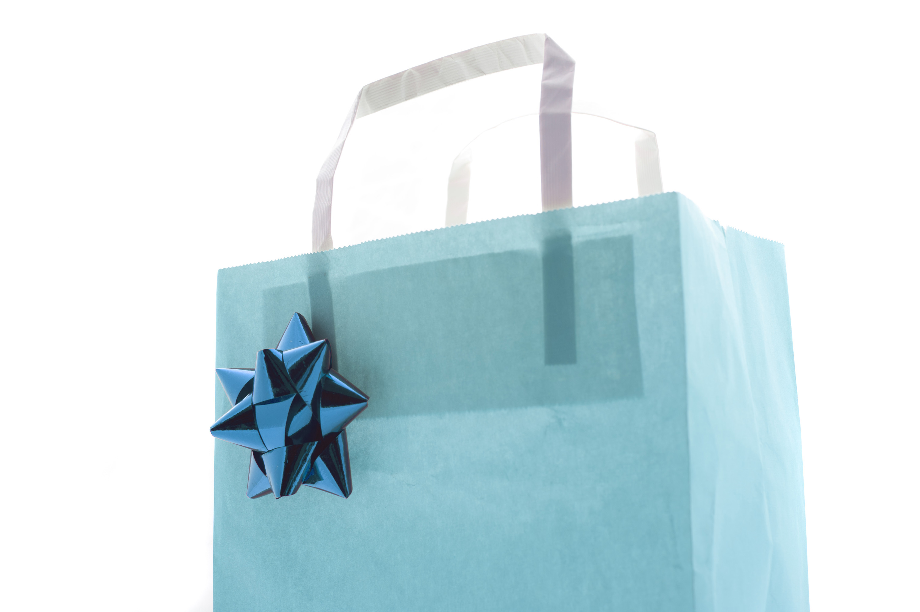 Festive blue gift bag decorated with a matching bow against a high key white background