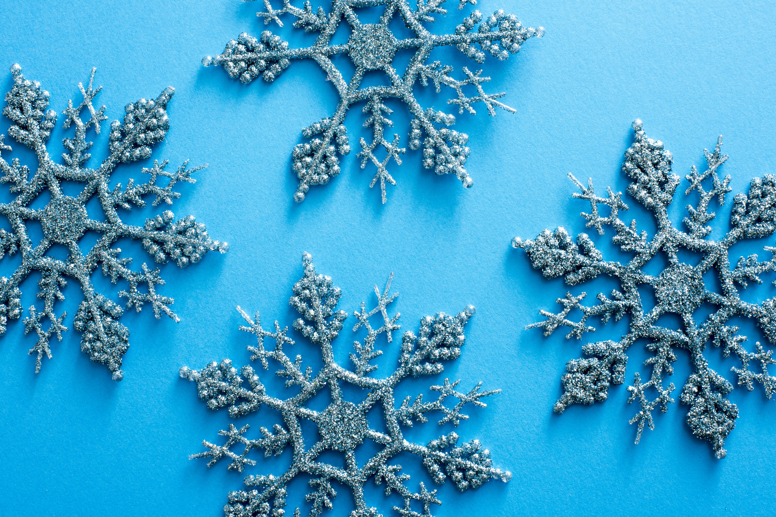 Blue glitter Christmas snowflake decorations arranged on a matching background for a festive holiday pattern