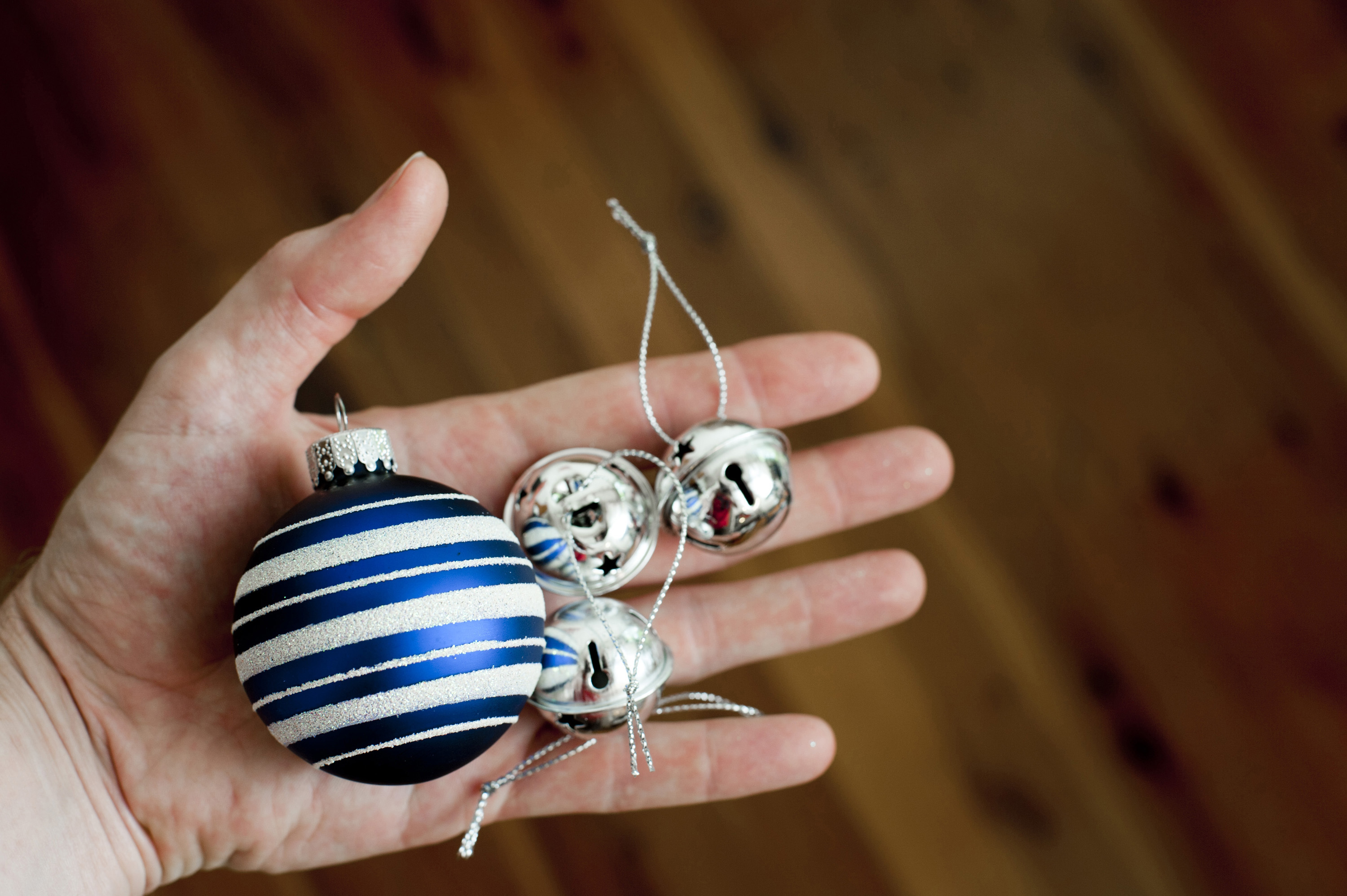 Close up shot of a hand with a blue bauble and some metallic closed bells