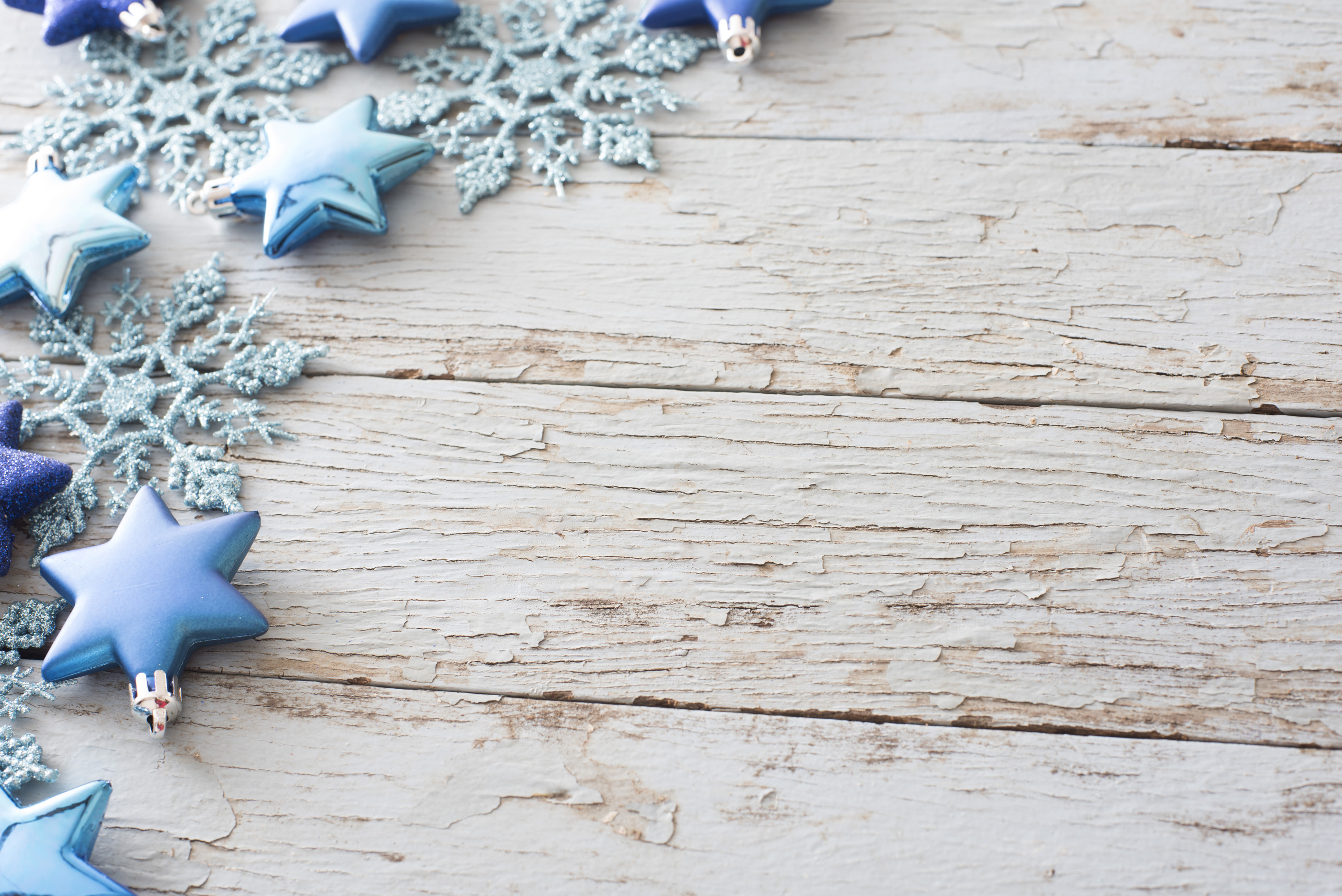 Rustic Christmas corner decoration on wood with scattered blue stars and glitter snowflakes and copy space for your holiday greeting