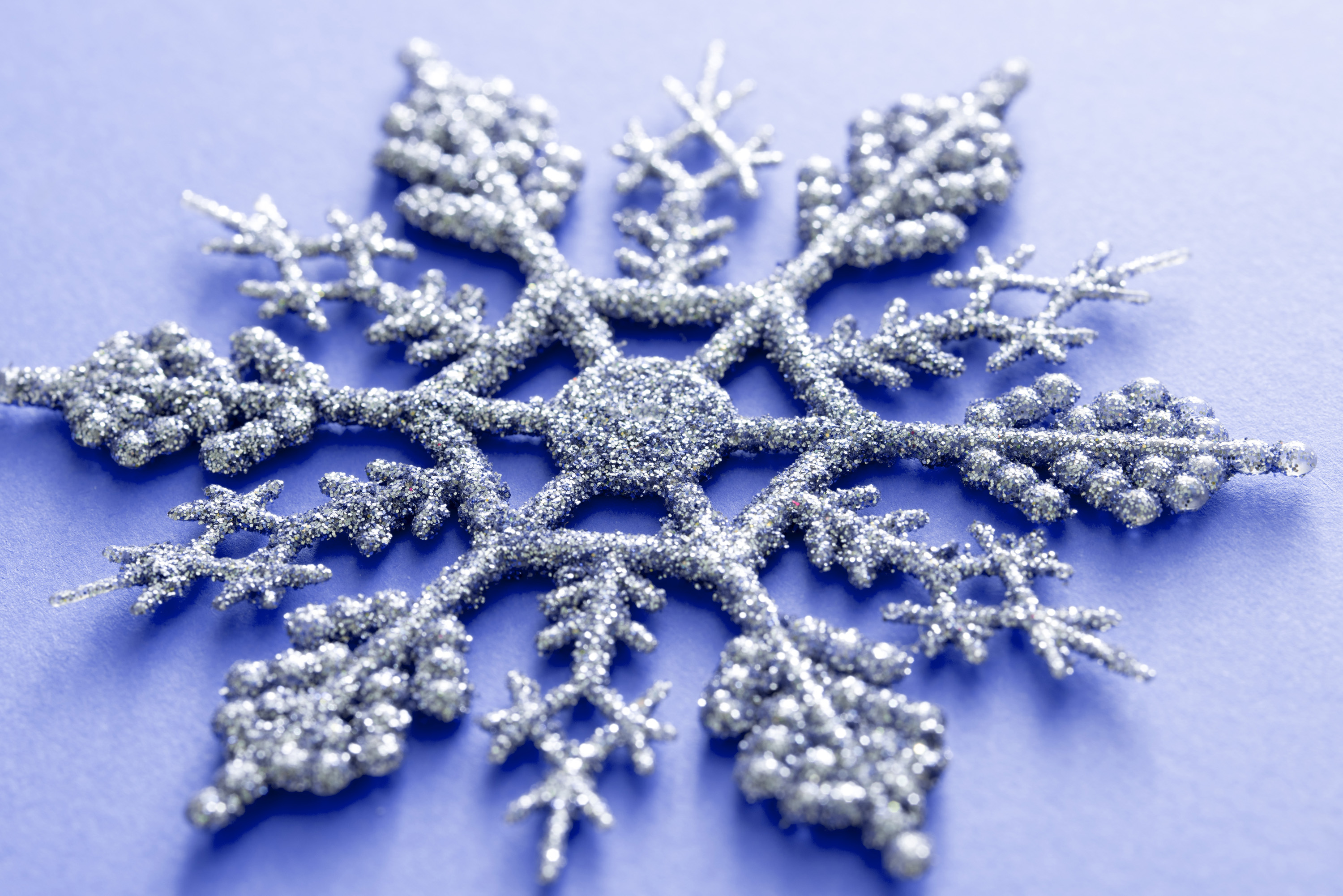 Ornamental silver glitter Xmas snowflake on a blue background viewed close up for a festive Christmas background