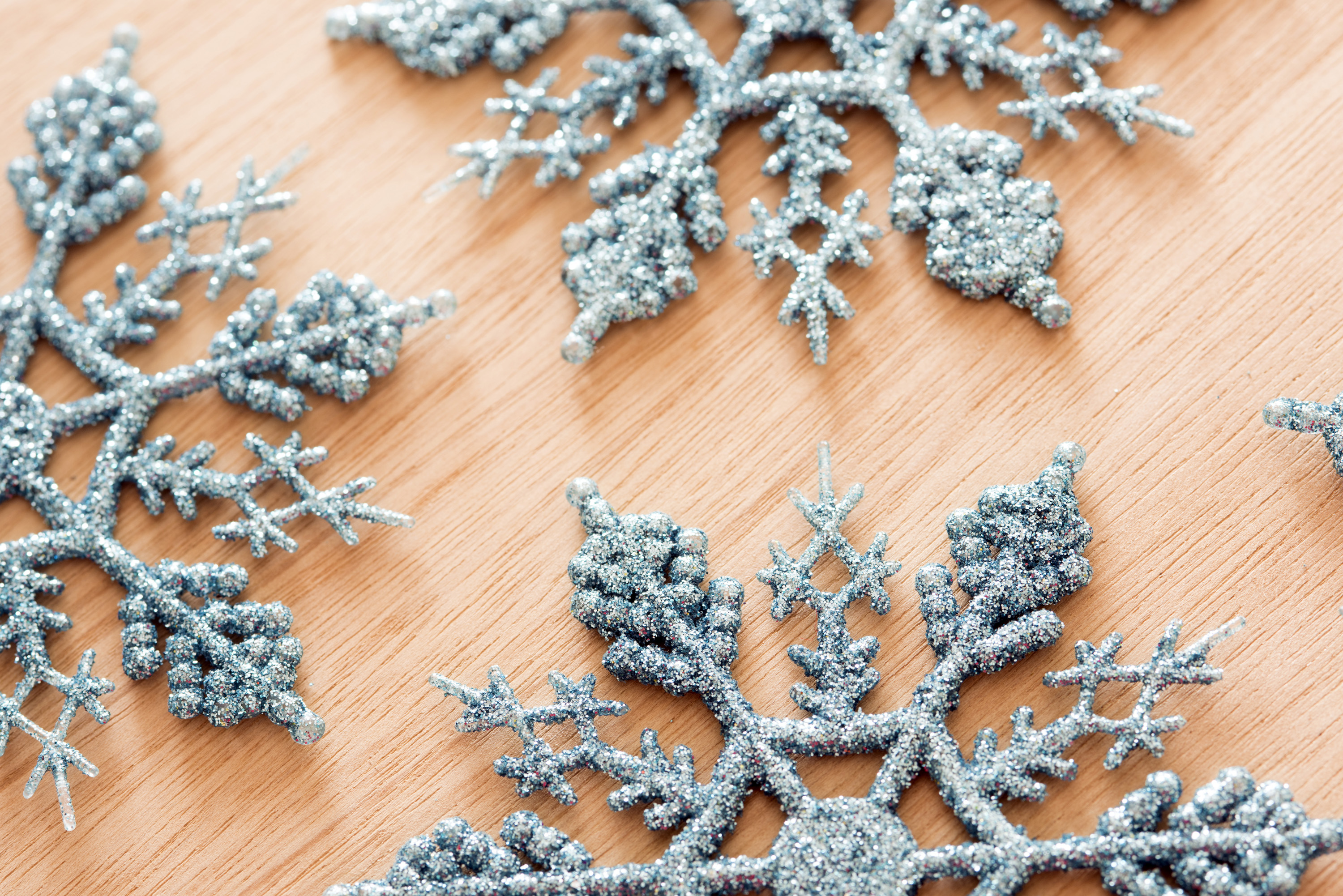 Tasteful ornamental blue glitter snowflake decorations for Christmas celebrations arranged on a wooden background in a high angle view