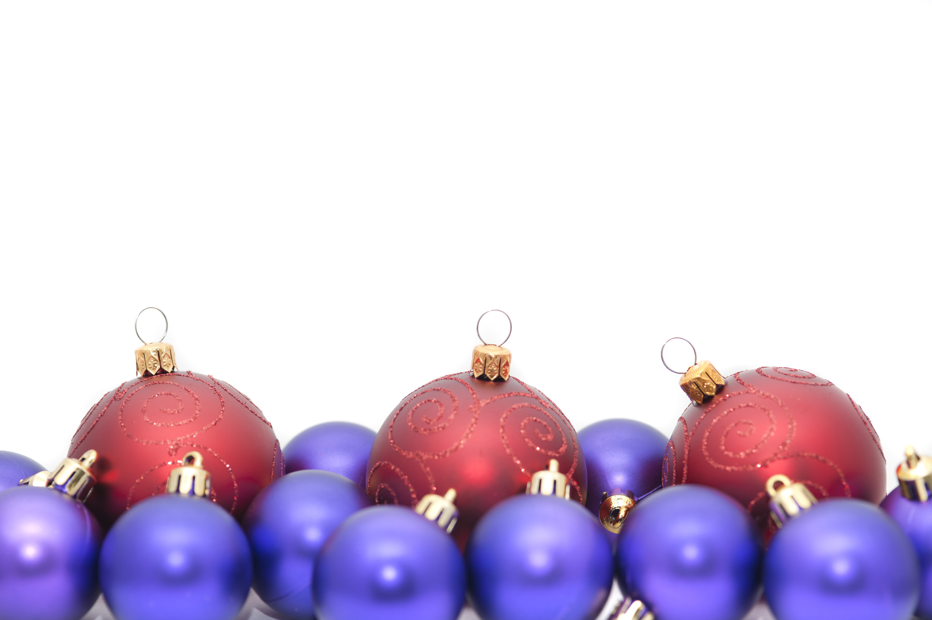 Colourful Christmas bauble border with red and purple balls arranged along the lower edge of the frame with copyspace above