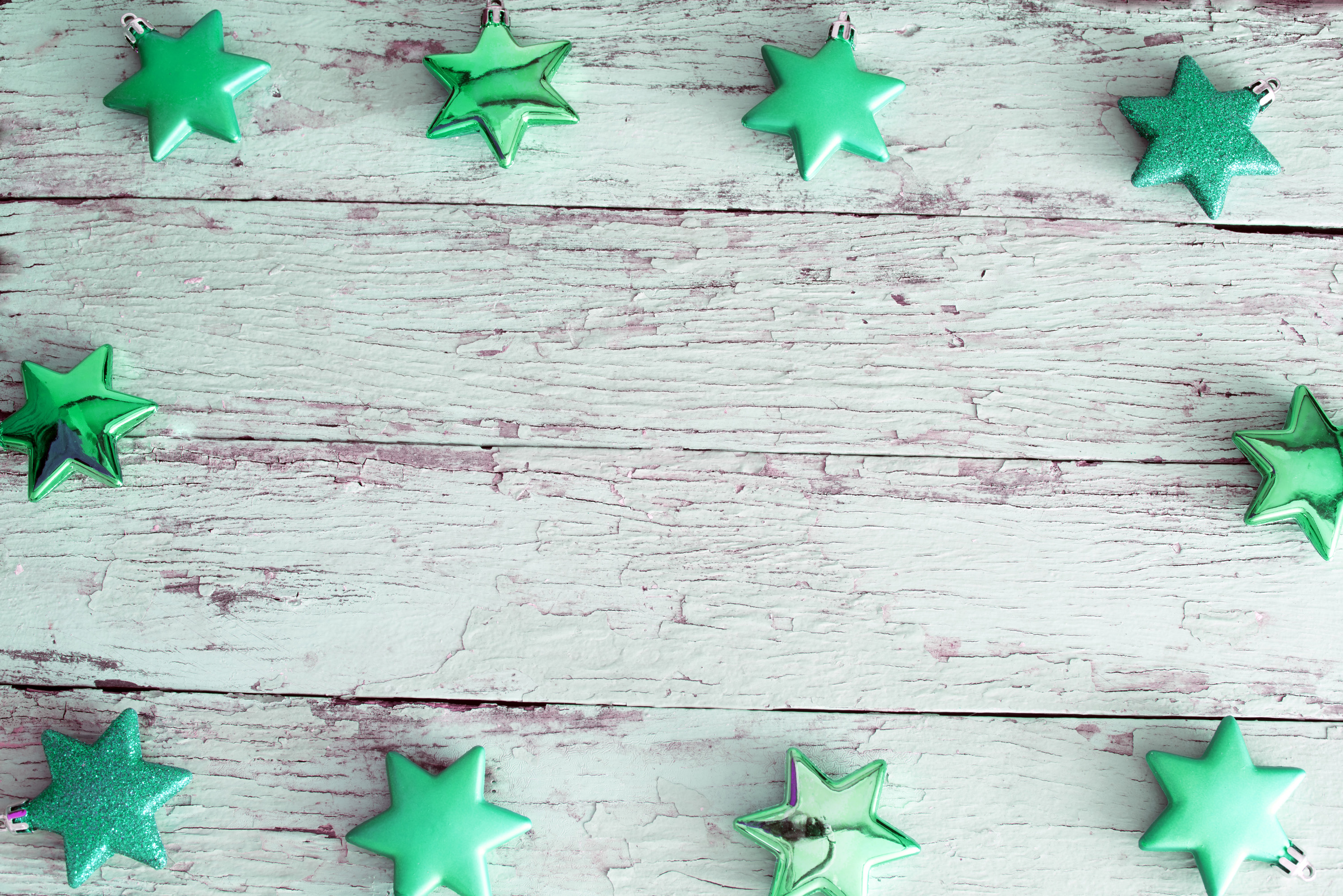Green Christmas star border on rustic weathered white painted wood with central copy space for your holiday greeting