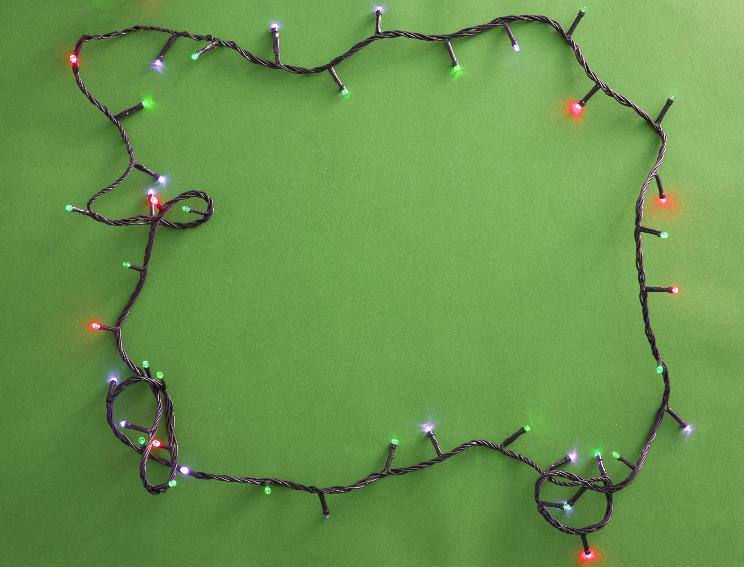 Festive lighted garland on green background. From above