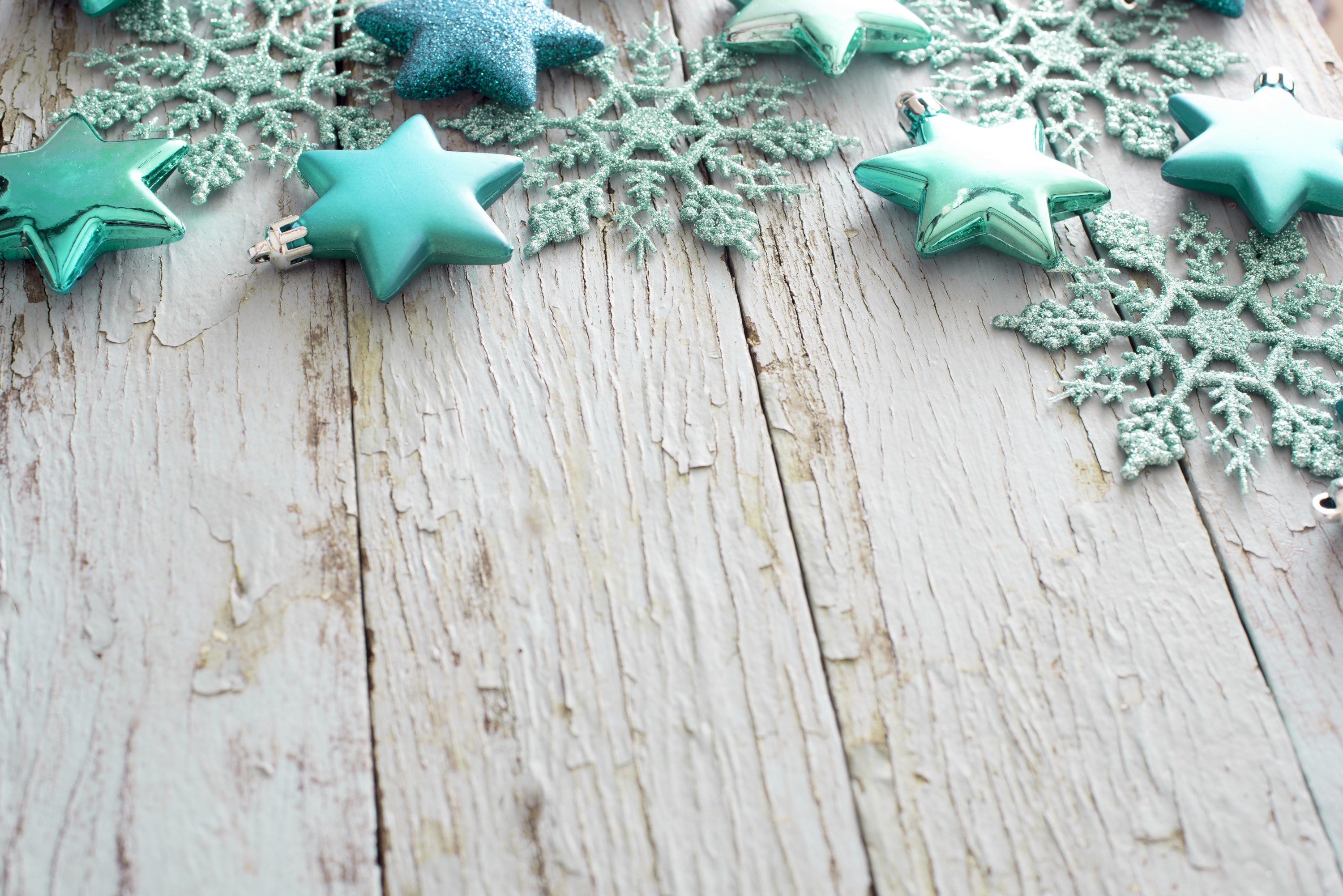 Rustic green Christmas border of delicate snowflake and star ornaments on old weathered textured wood with copy space
