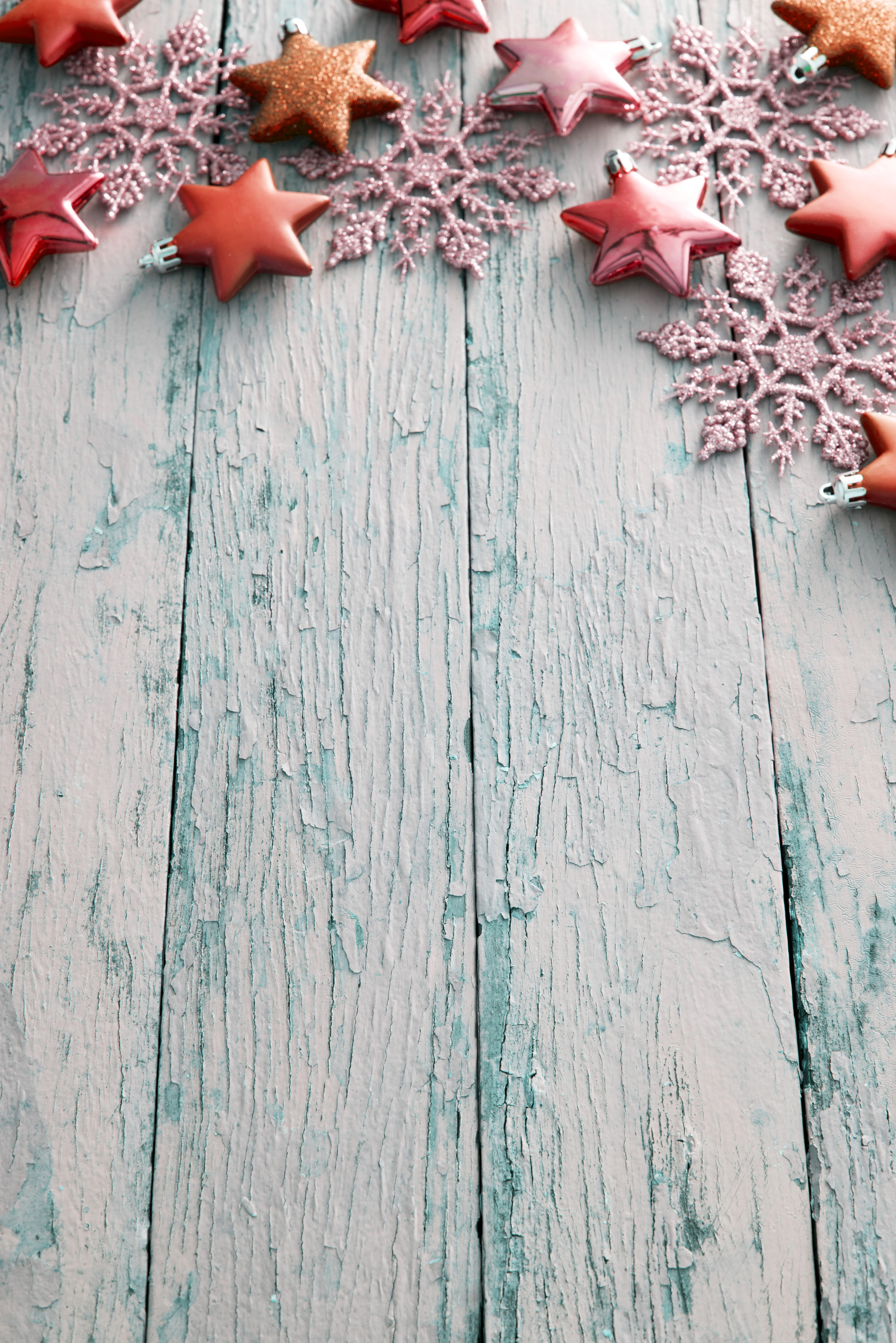 Rustic Christmas border of orange stars and snowflakes on blue textured weathered wood with copy space, oblique angle view