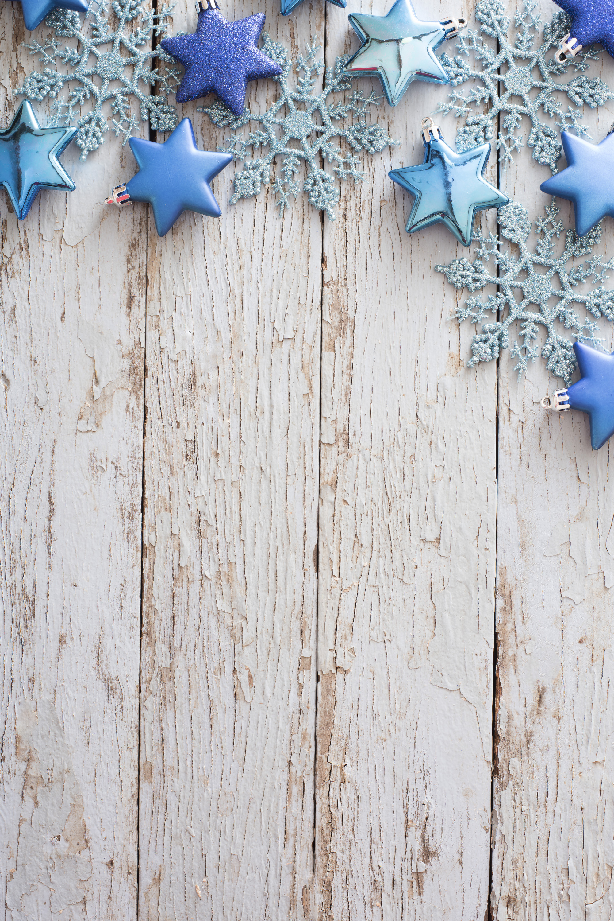 Border of blue Christmas ornaments with glitter snowflakes and stars on rustic white wood with cracks, peeling paint and copy space