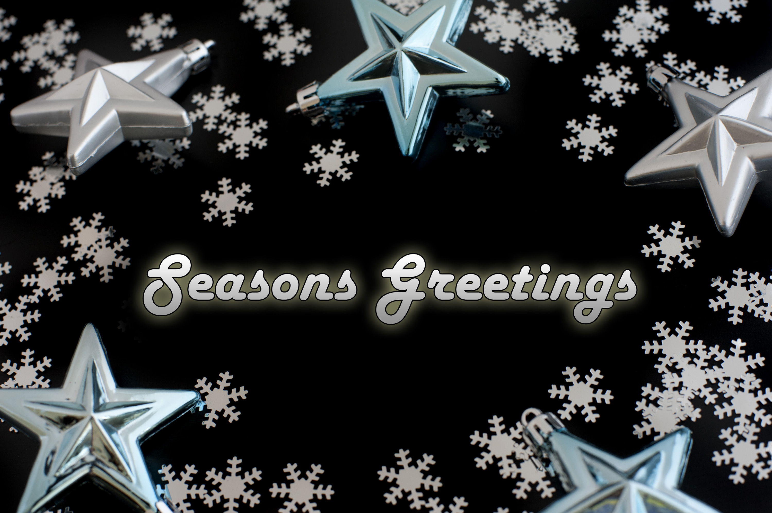 Seasons greetings card with glowing text surrounded by snowflakes and stars on a black background