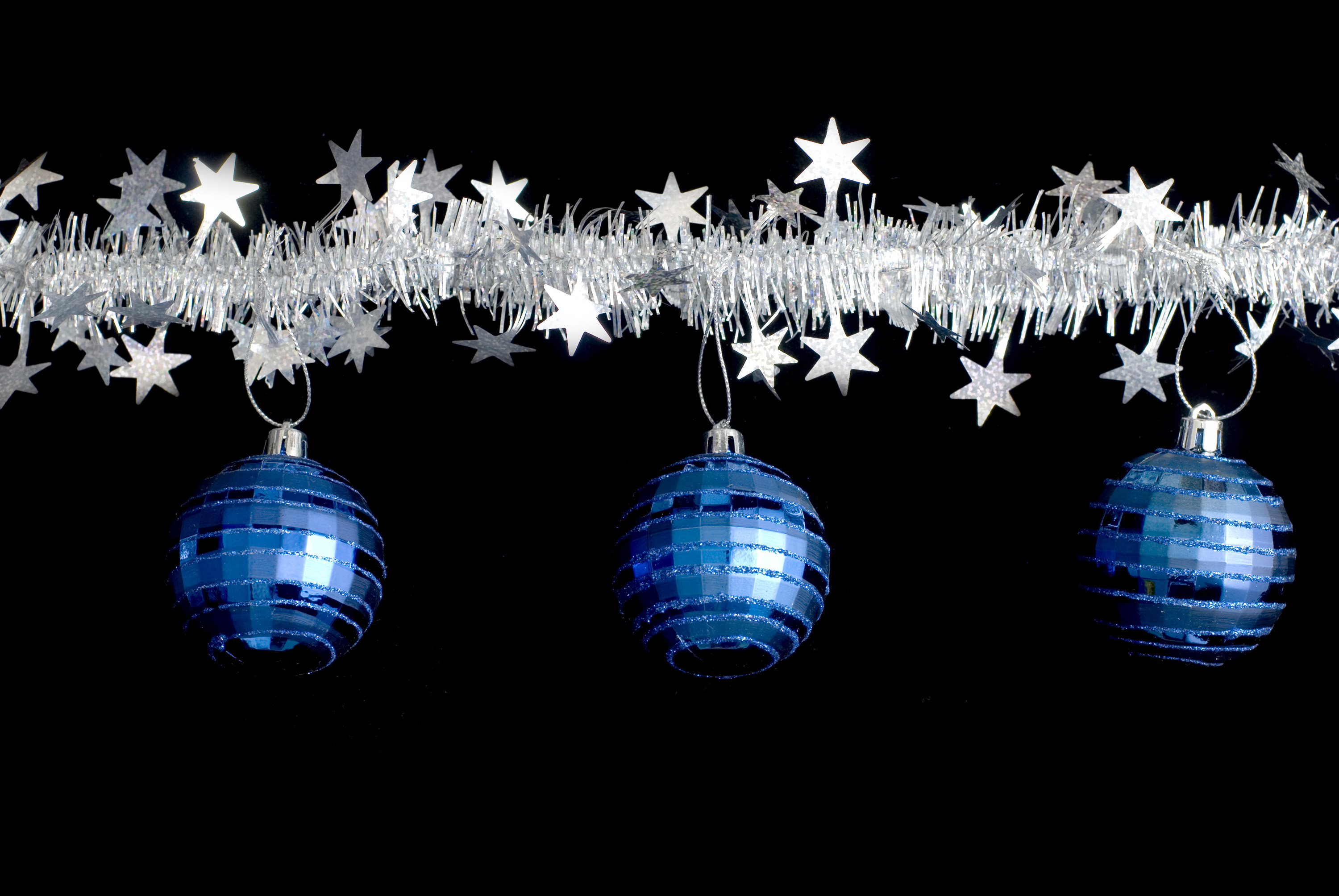 a line of christmas tinsel and and three hanging christmas balls