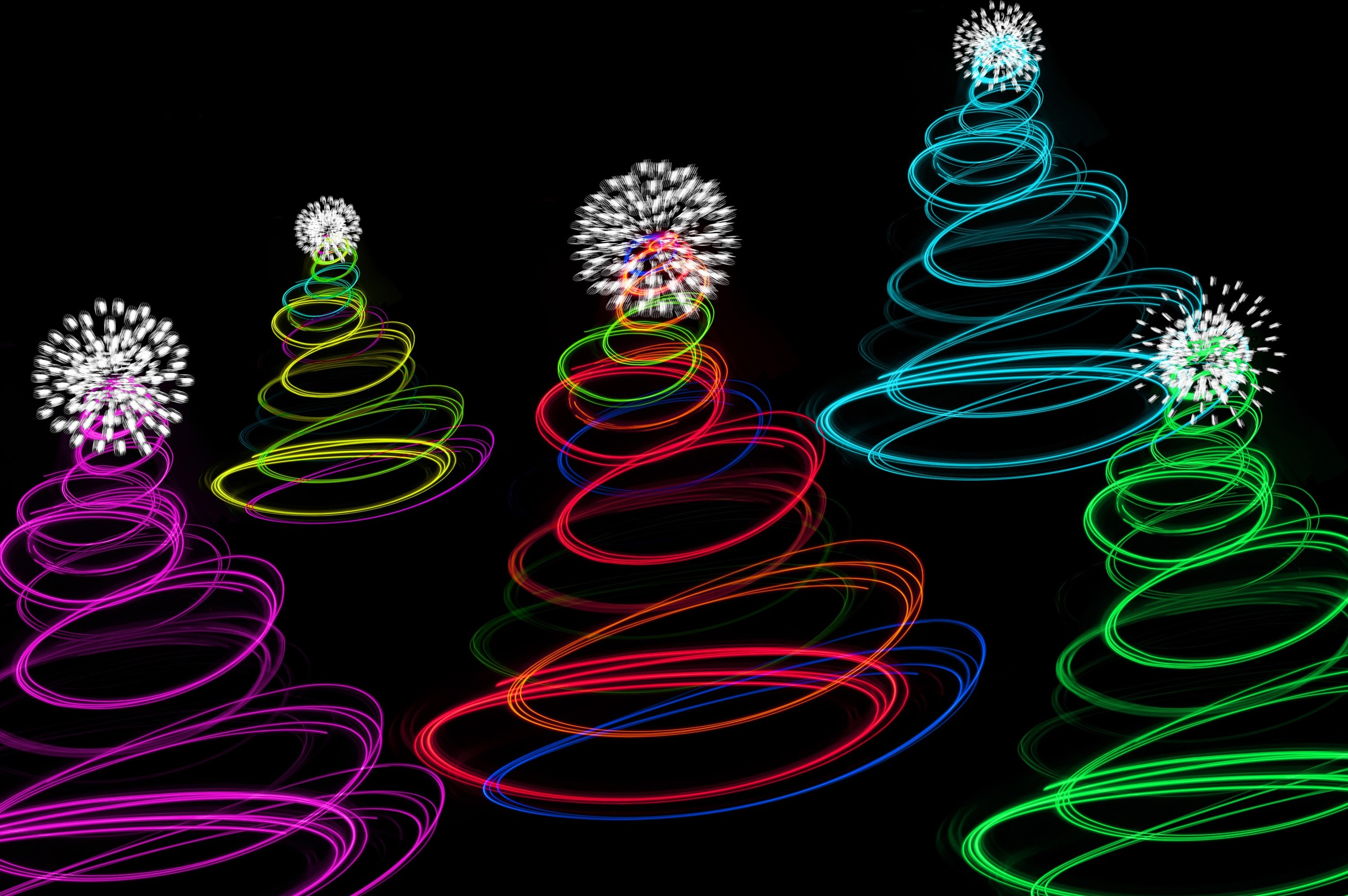 Abstract Christmas tree lights with a twirled shape and twinkling decorations on the top in the colours of the rainbow or spectrum on a black background