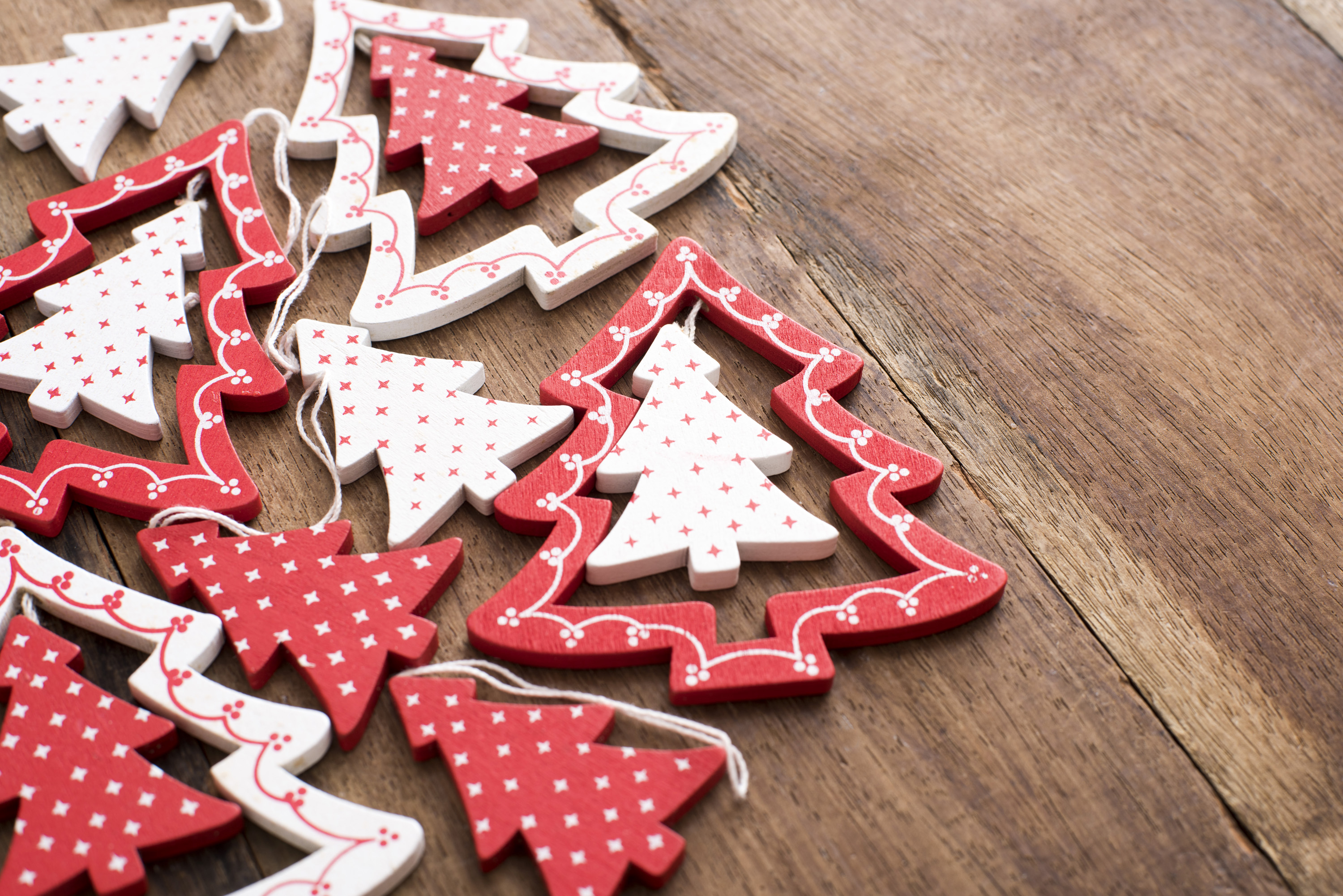 Assorted red and white wooden tree ornaments for celebrating Christmas forming a side border on a wood table with copy space