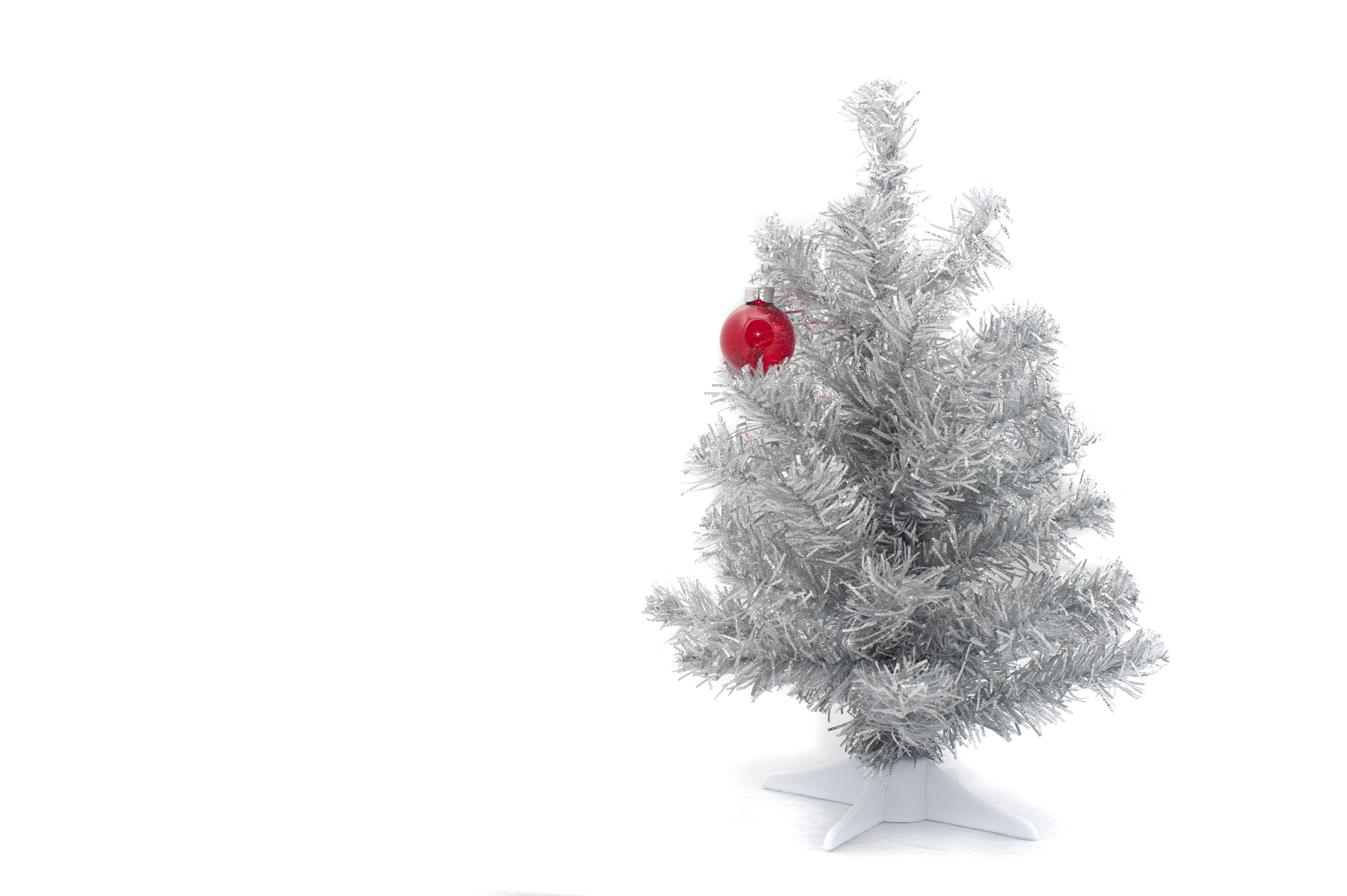 austere christmas, an artifcial christmas tree and a single red decoration