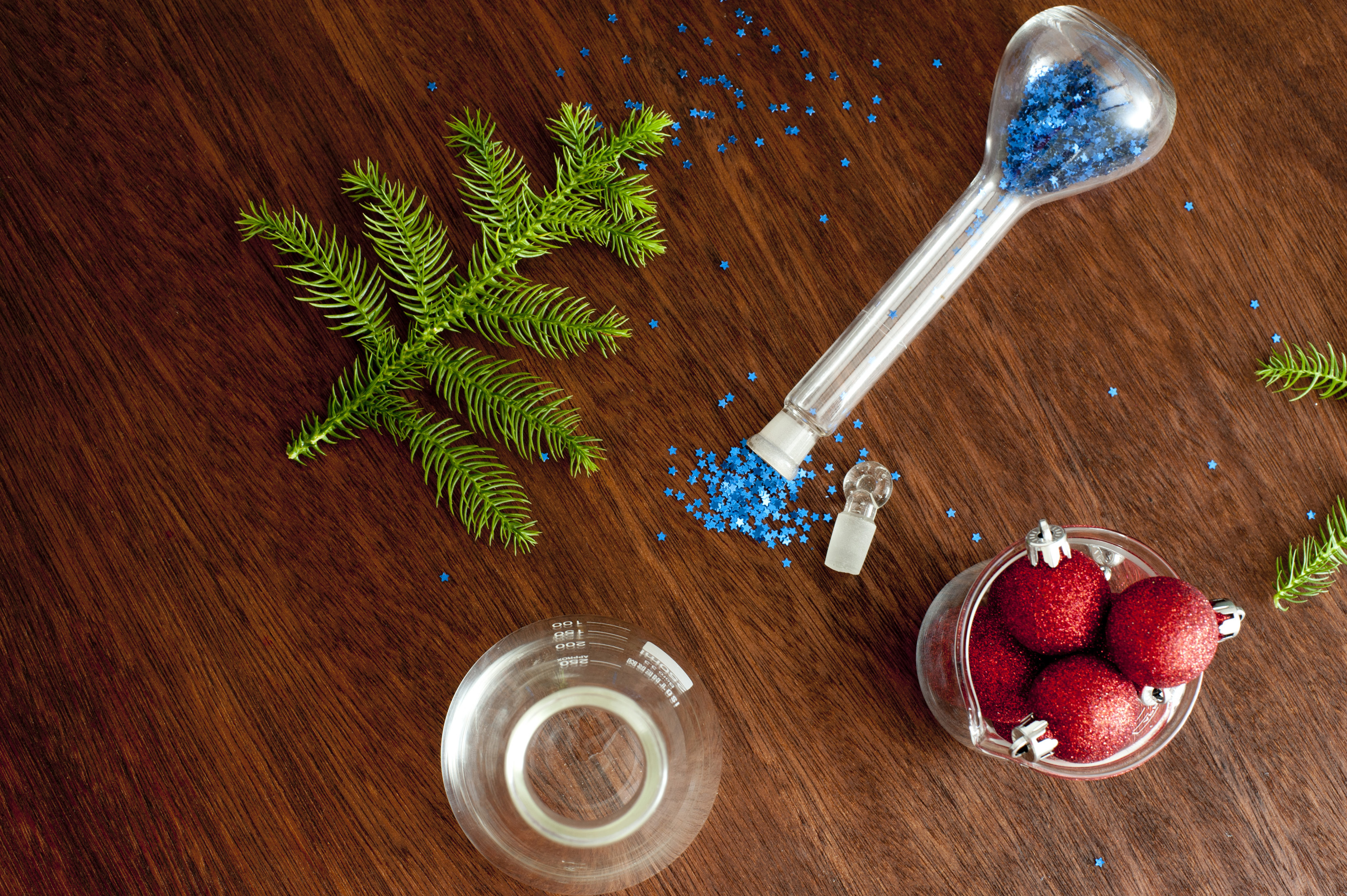 red Christmas balls and fir tree branch on wooden surface with chemistry beakers