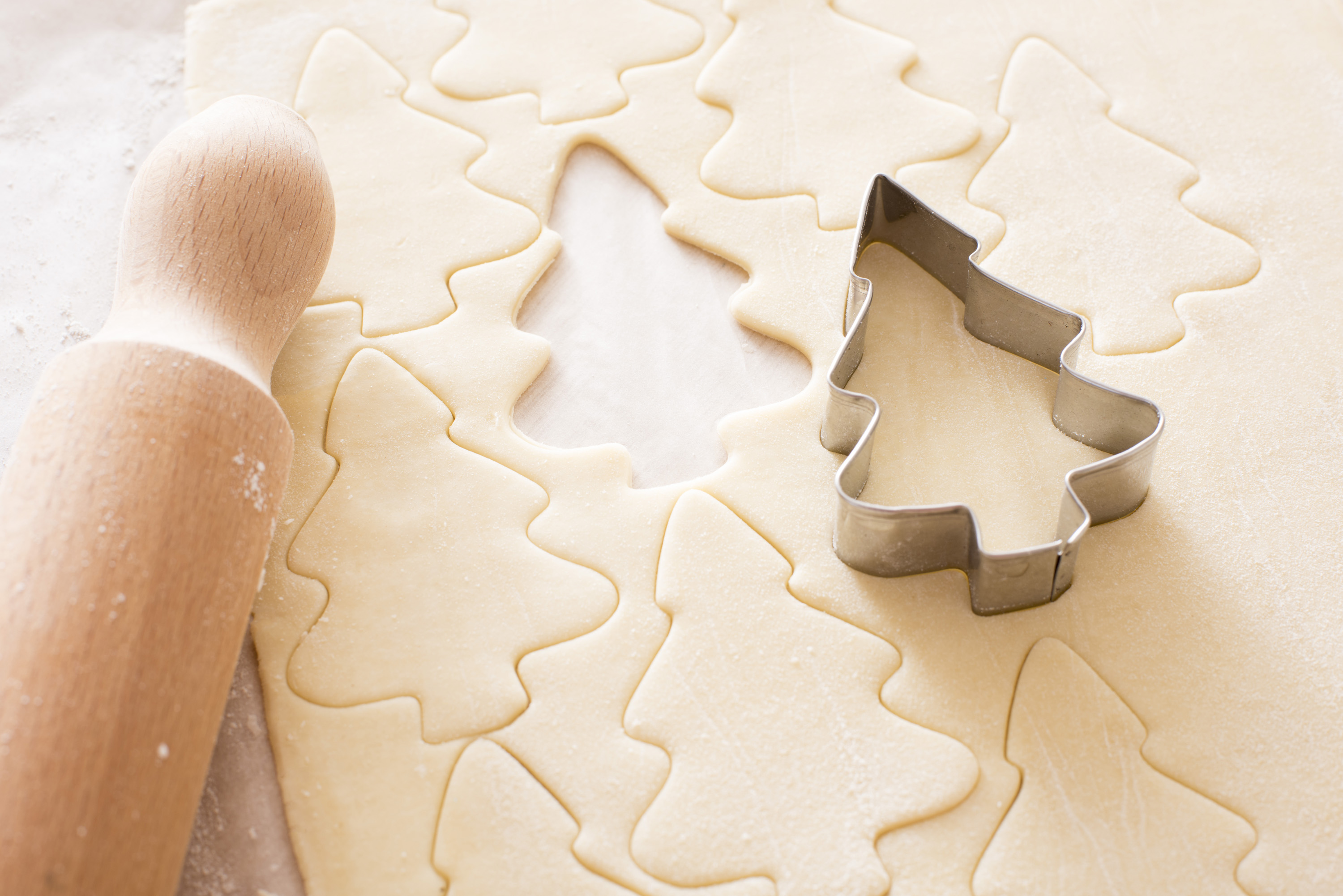 Baking tree shaped Christmas cookies at home with a metal cookie cutter, rolling pin and cut out shape on neatly rolled and trimmed dough