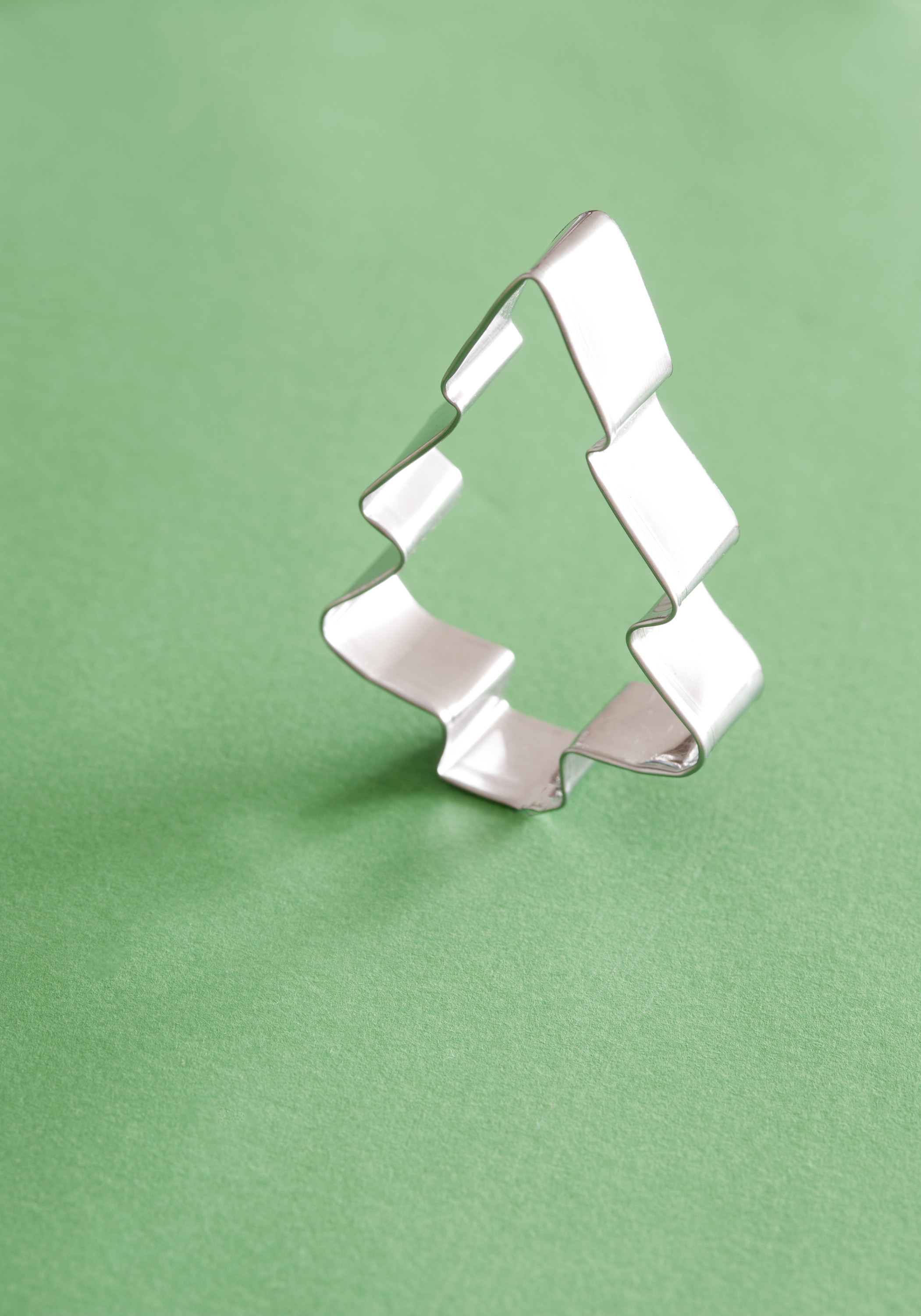 Close-up of Christmas tree cookie cutter on green table