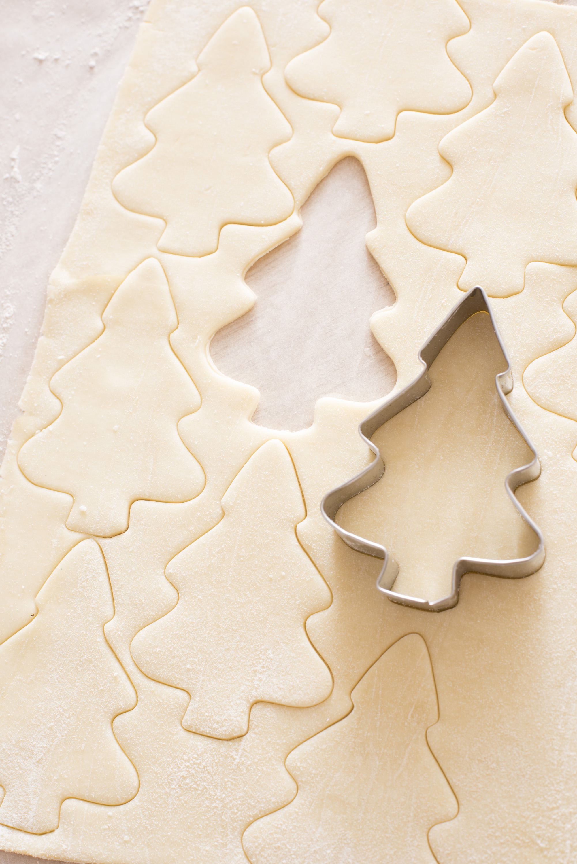 Close up of a sheet of dough with a cutter in shape of a christmas tree